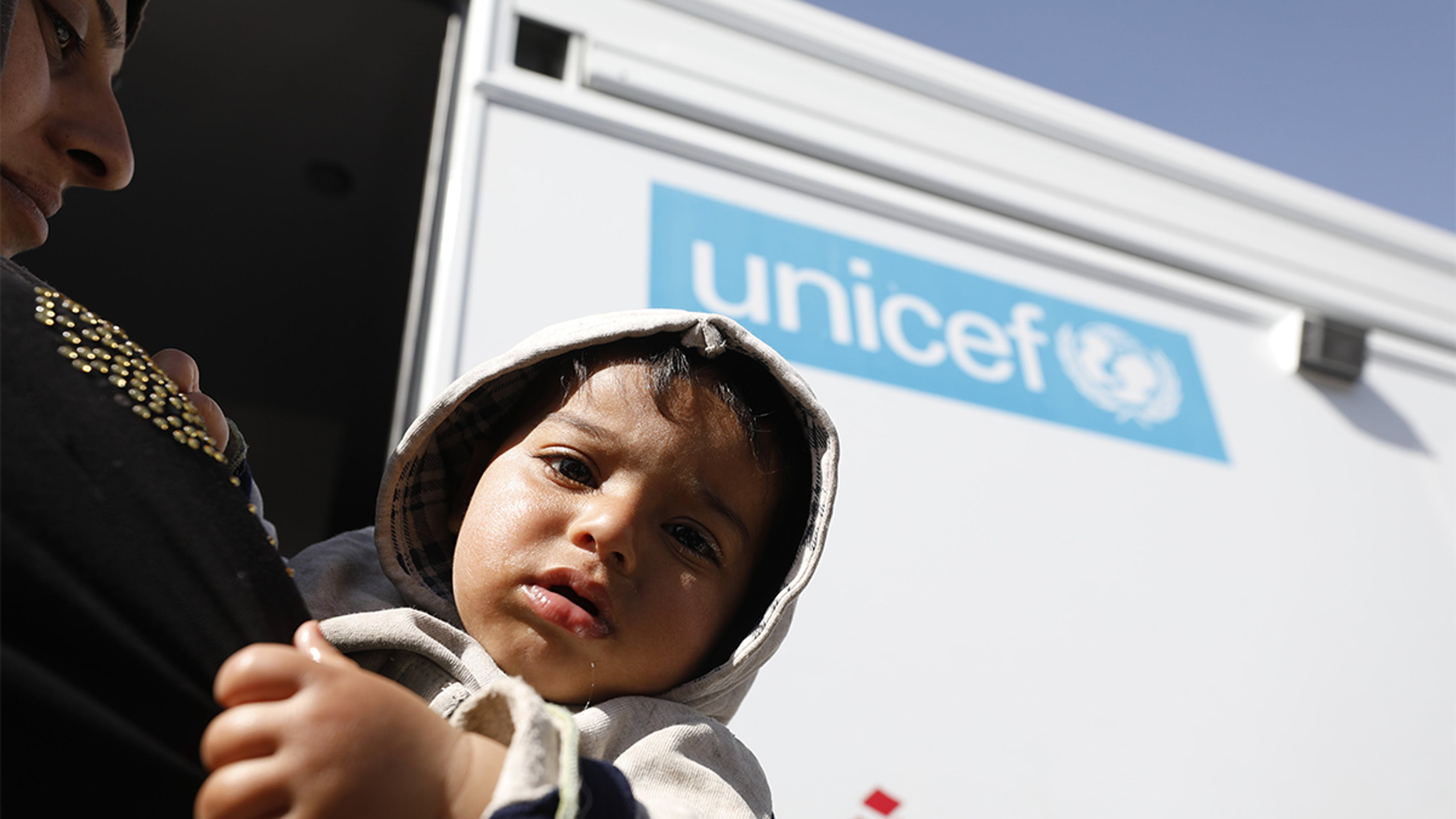 Siria,un bambino e sua madre entrano nella clinica sanitaria mobile supportata dall'UNICEF