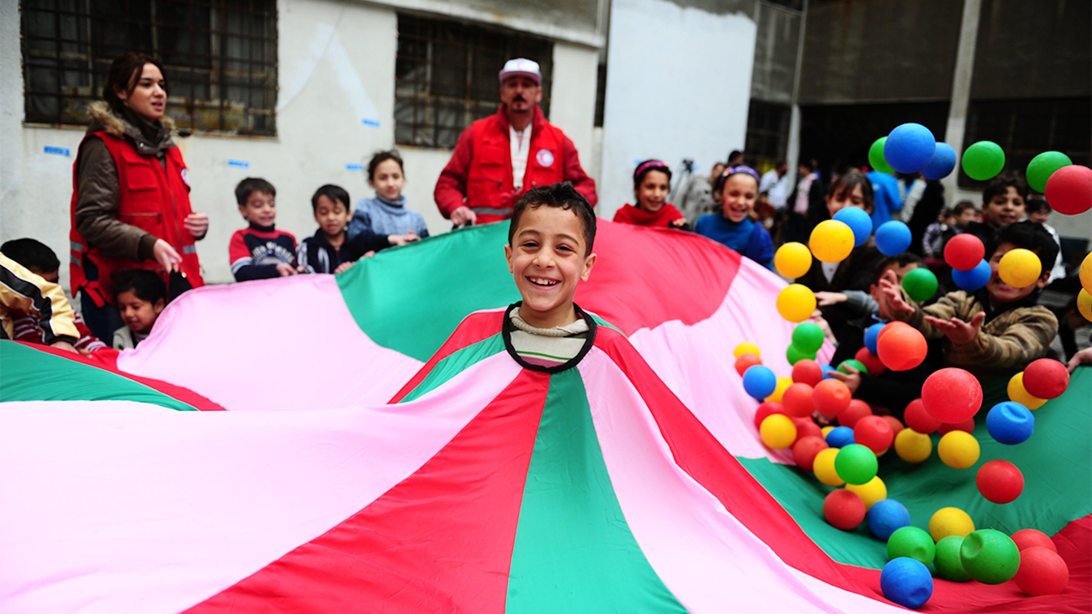 Siria, bambini sorridono durante un'attività ricreativa in un rifugio per famiglie sfollate a Homs