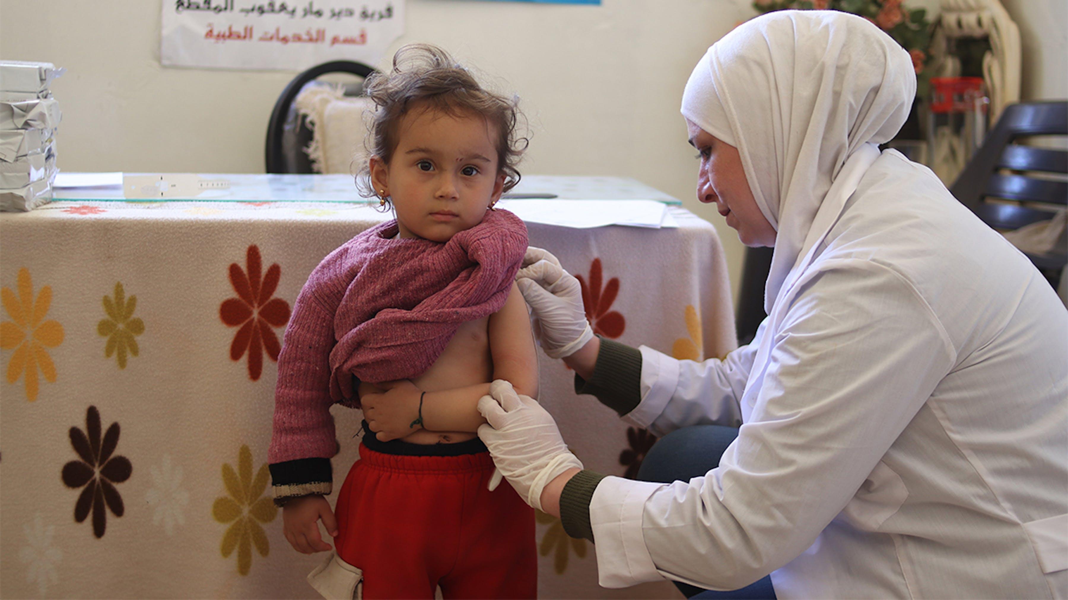 Siria, un'operatrice sanitaria visita Rahaf, 2 anni