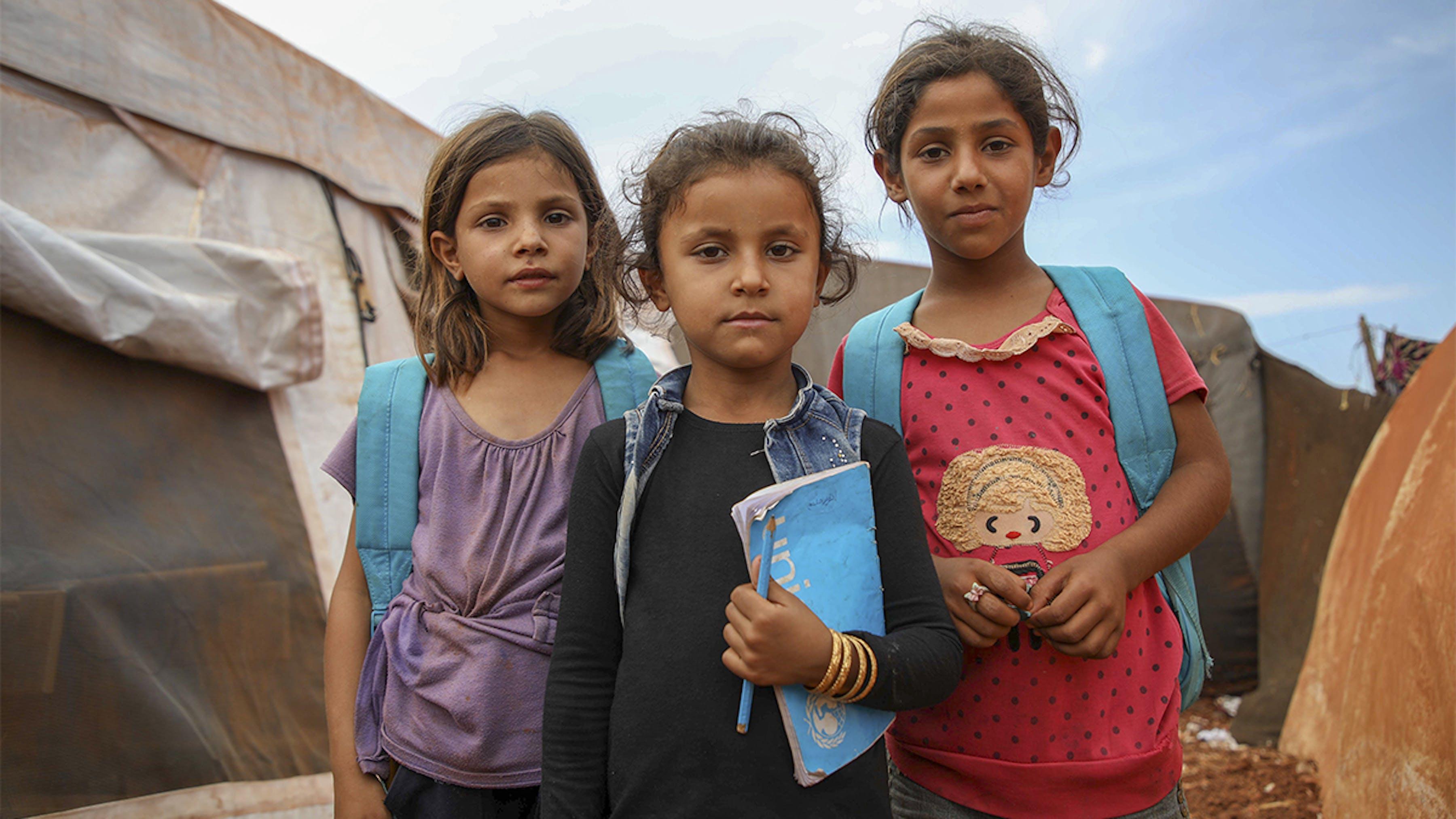 Siria, ragazze con zaini UNICEF fuori da una scuola allestita nel campo rifugiati