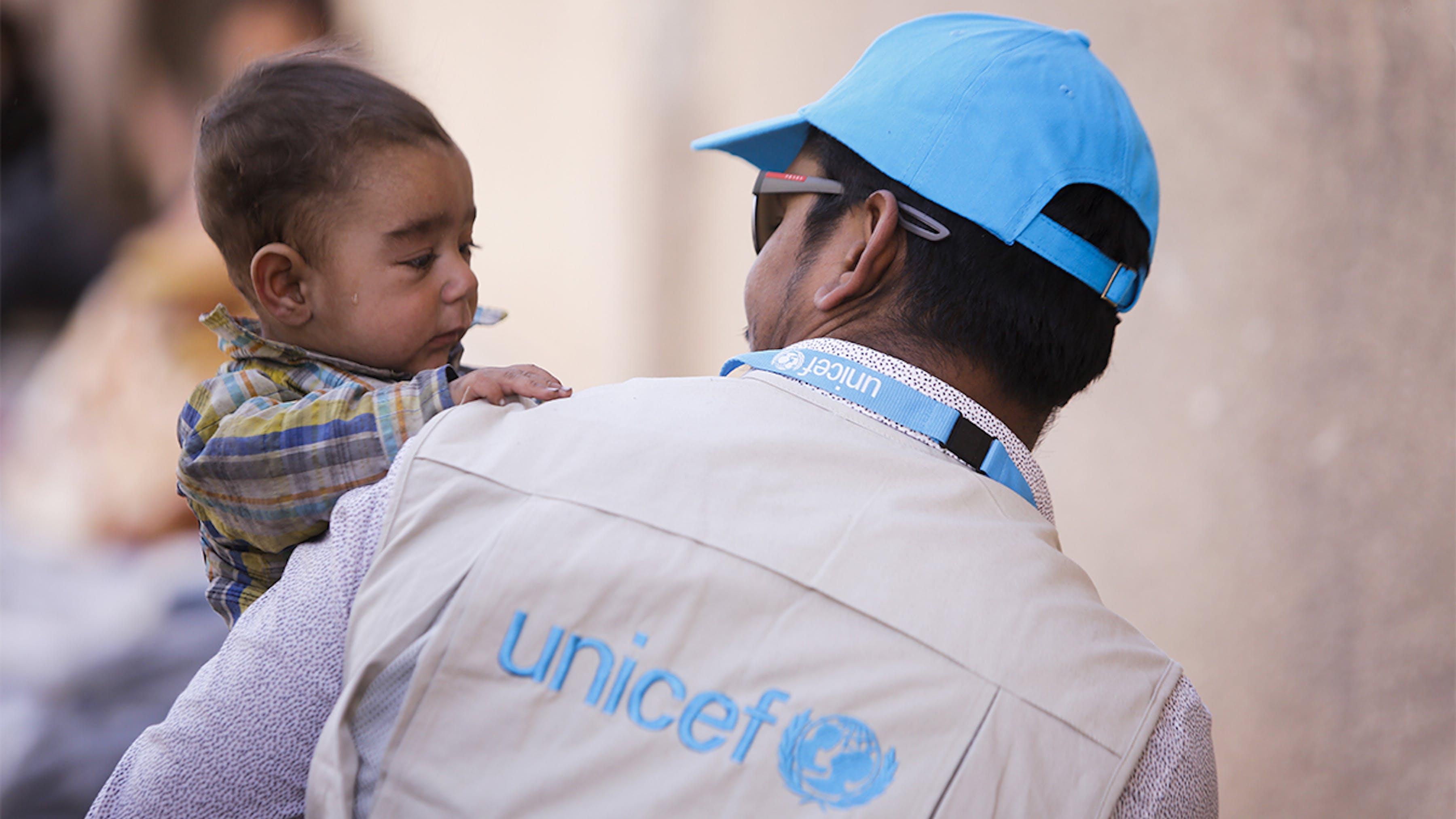 Siria, un bambino con un operatore dell'UNICEF