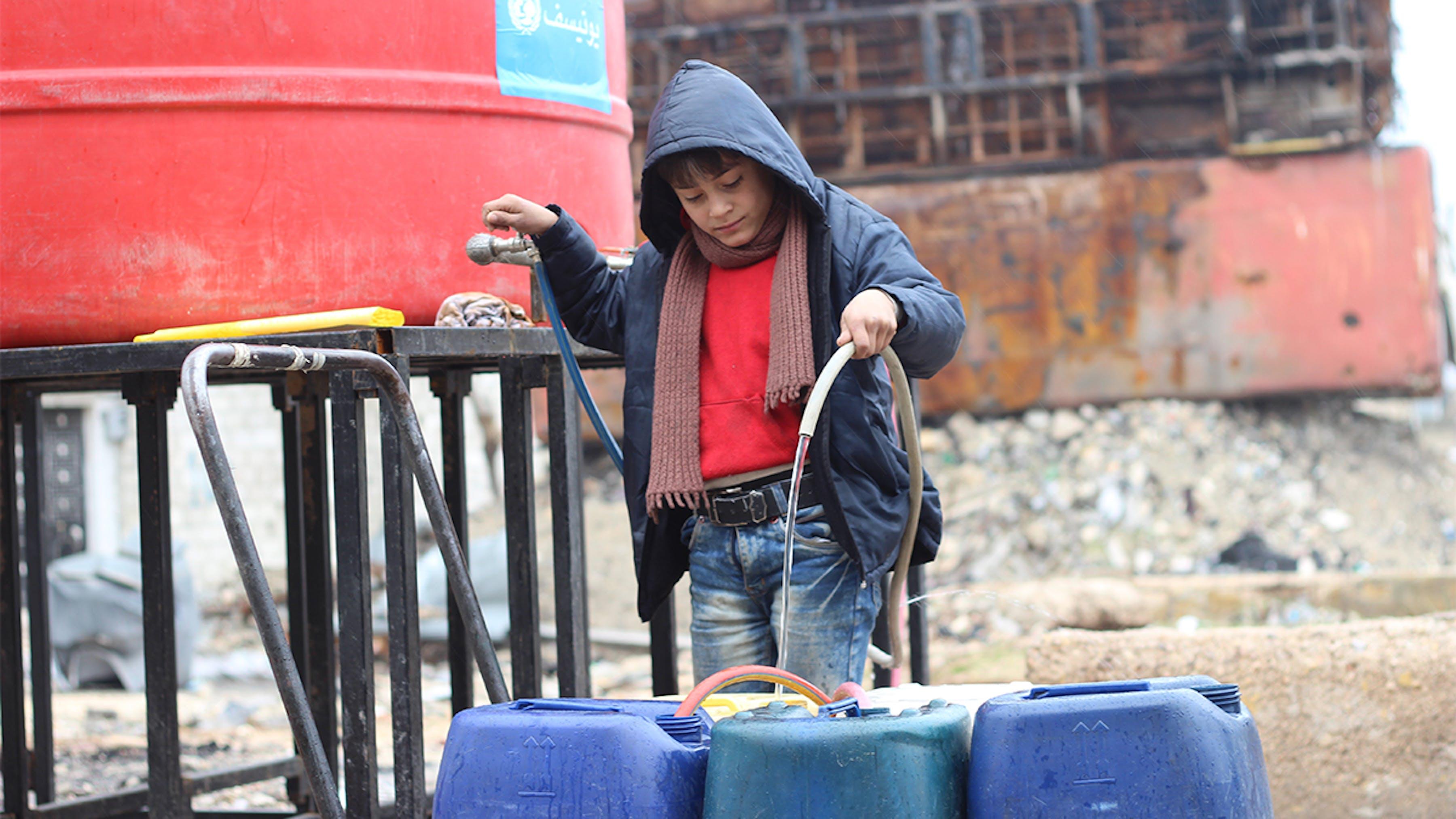 Siria, un ragazzo rifugiato riempie le taniche con acqua