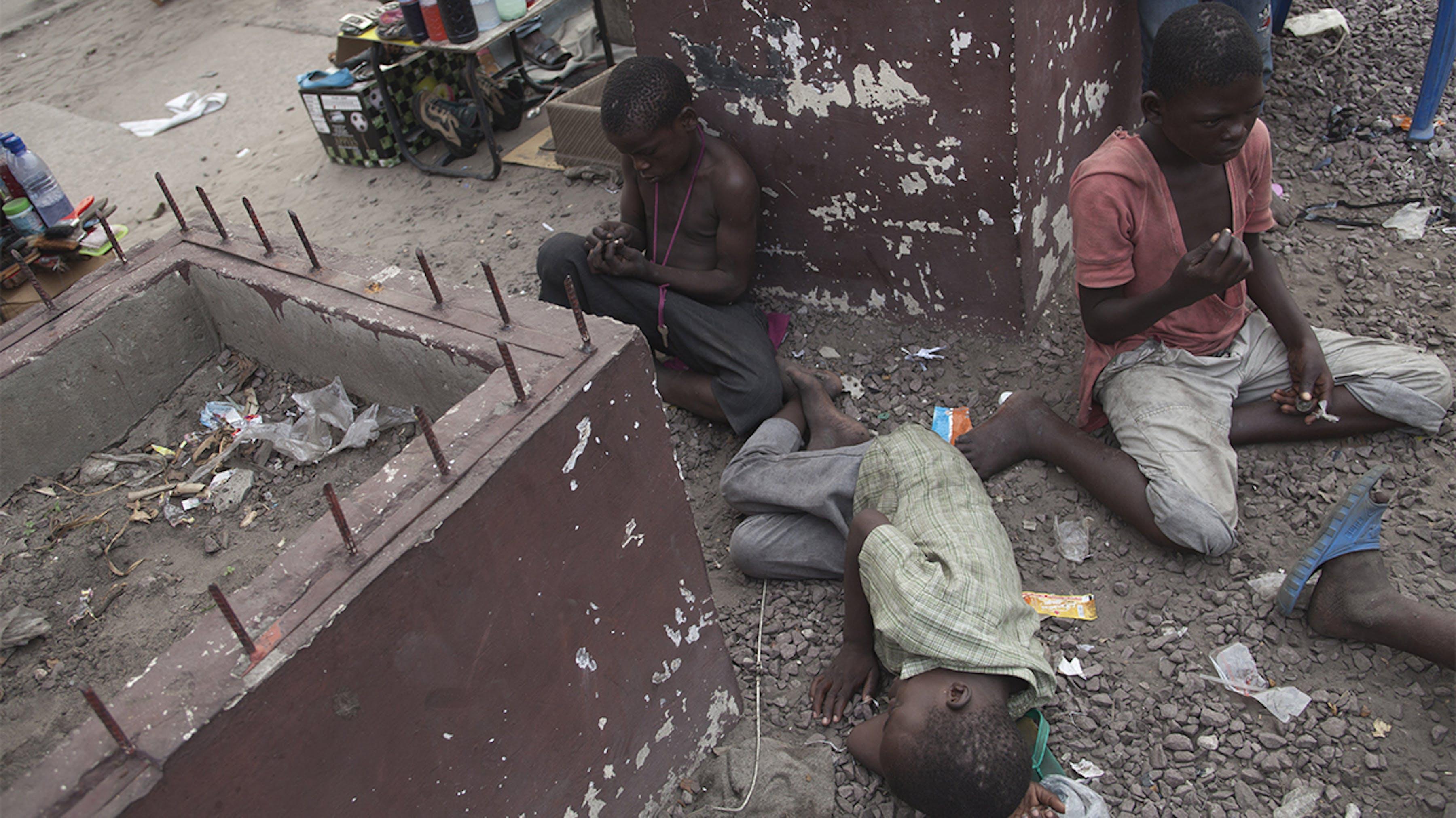 Congo, alcuni bambini di strada seduti o sdraiati a riposare.