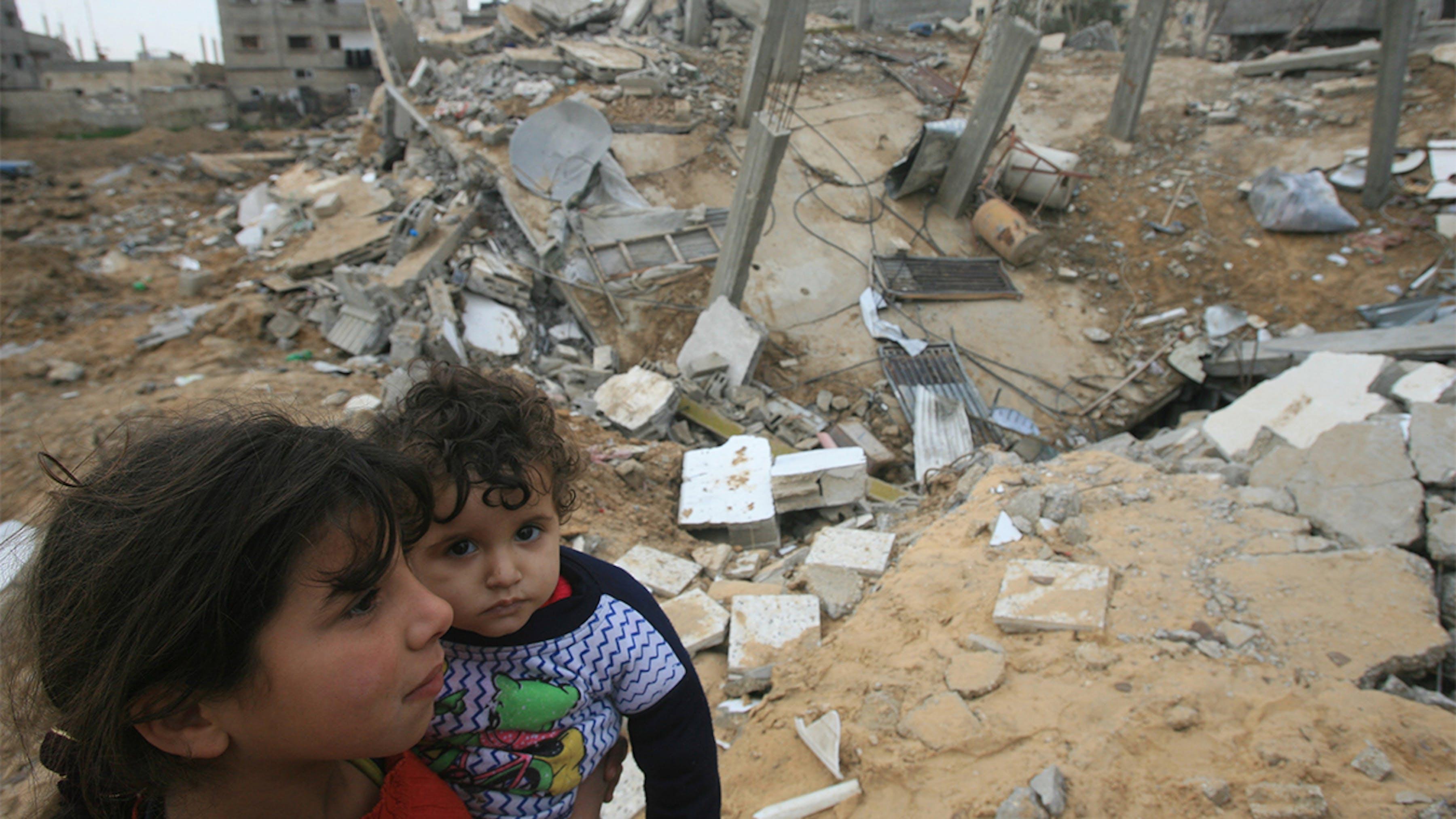 Palestina, bambini camminano in mezzo agli edifici distrutti.