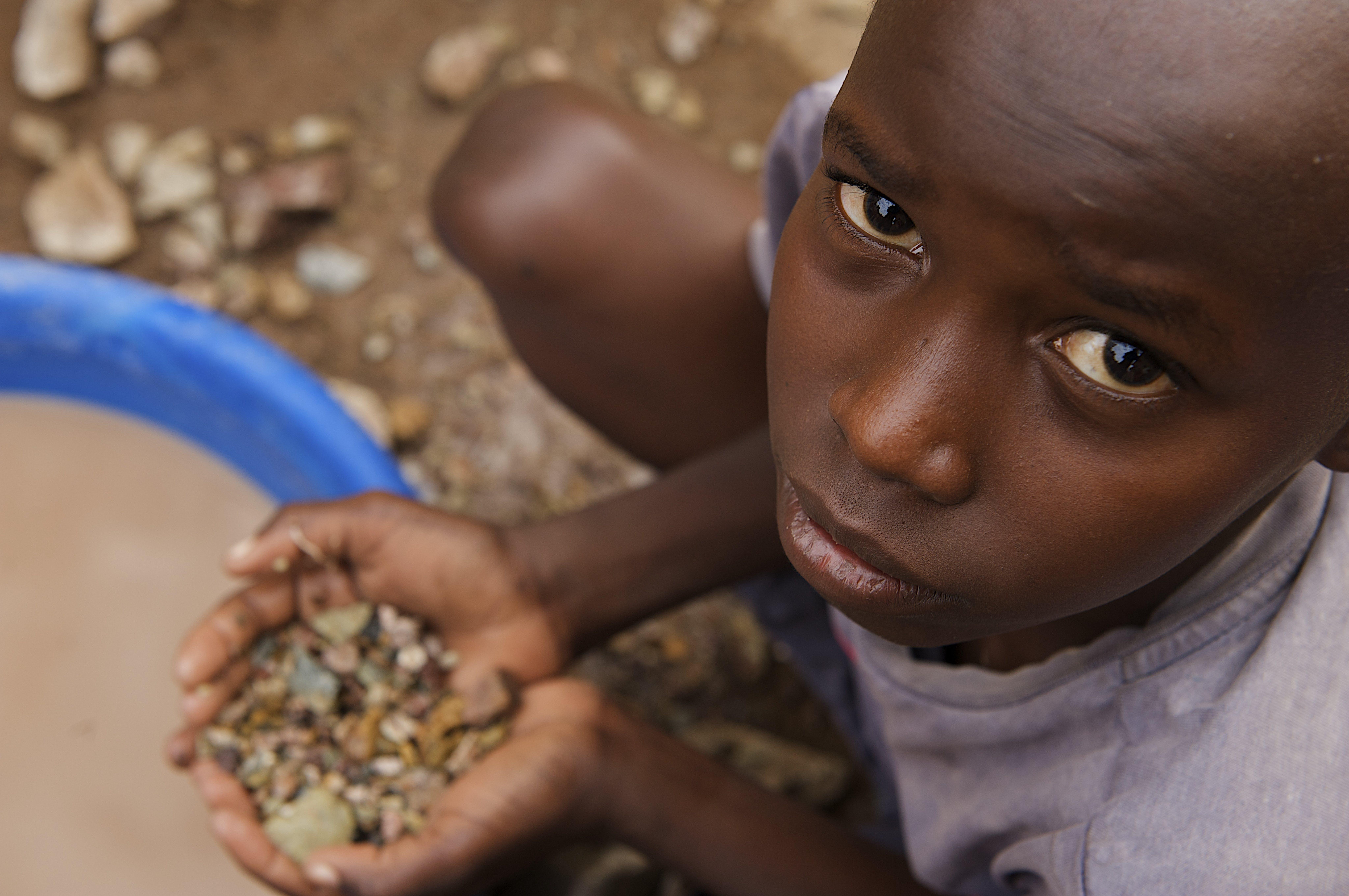 Tanzania, un bambino seduto a cercare oro tra le pietre, nella città mineraria di Nyamongo.