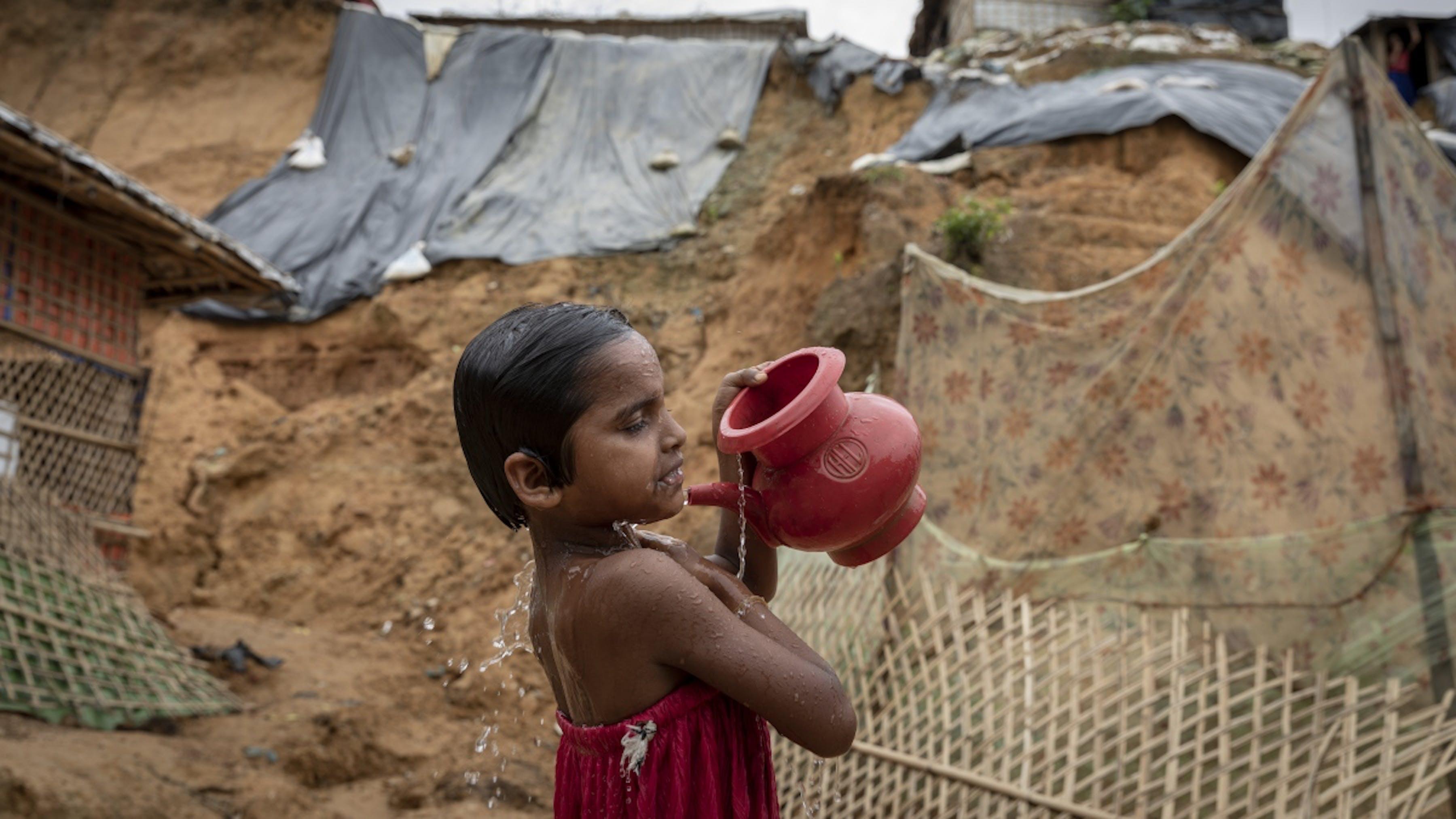 Bangladesh, una bambina si lava ai piedi di una collina a rischio frana nel campo di Cox's Bazar