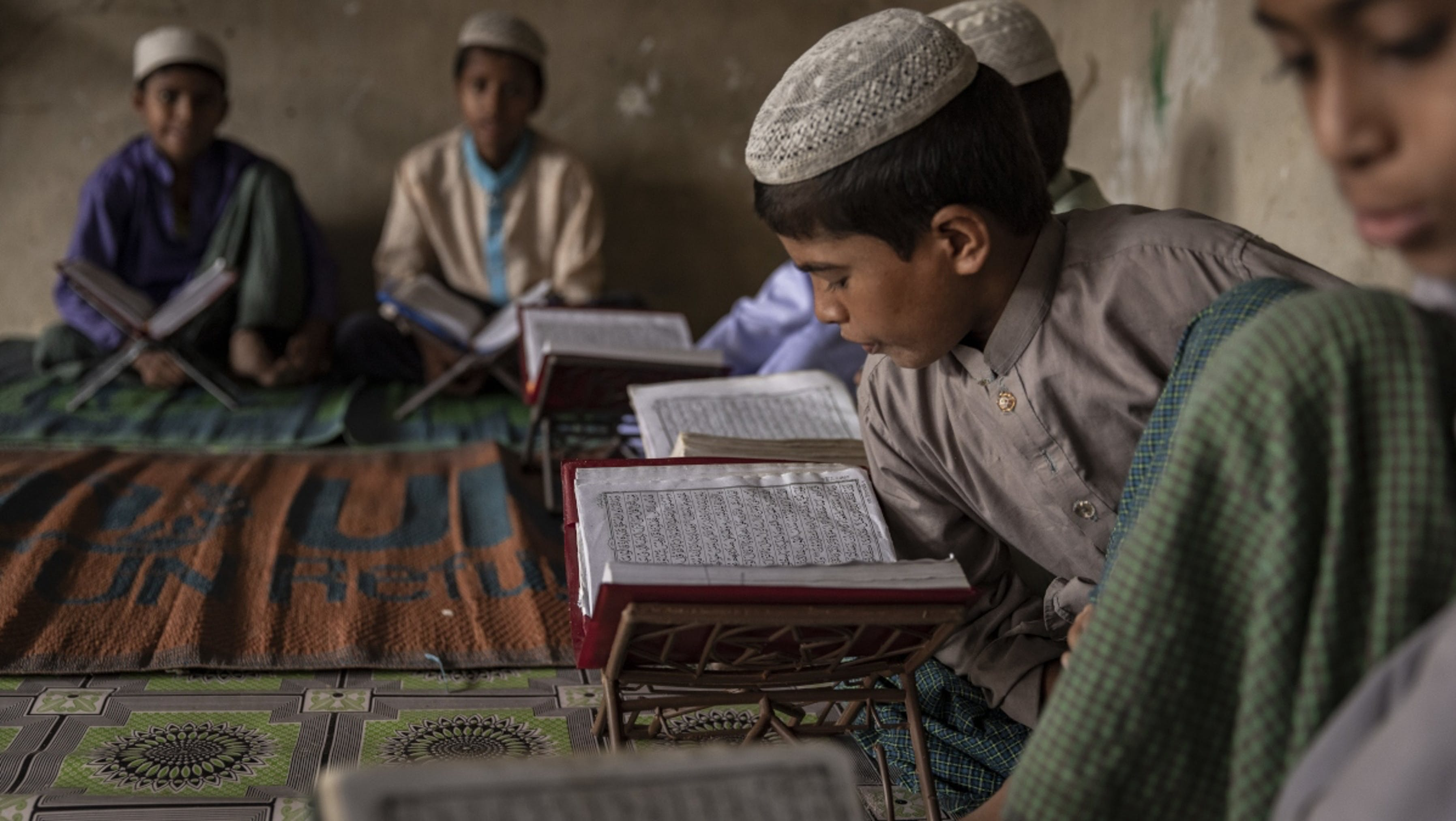 Bangladesh, un ragazzo legge dal suo libro di testo in una madrasa nel campo di Kutupalong-Balukhali, Cox's Bazar