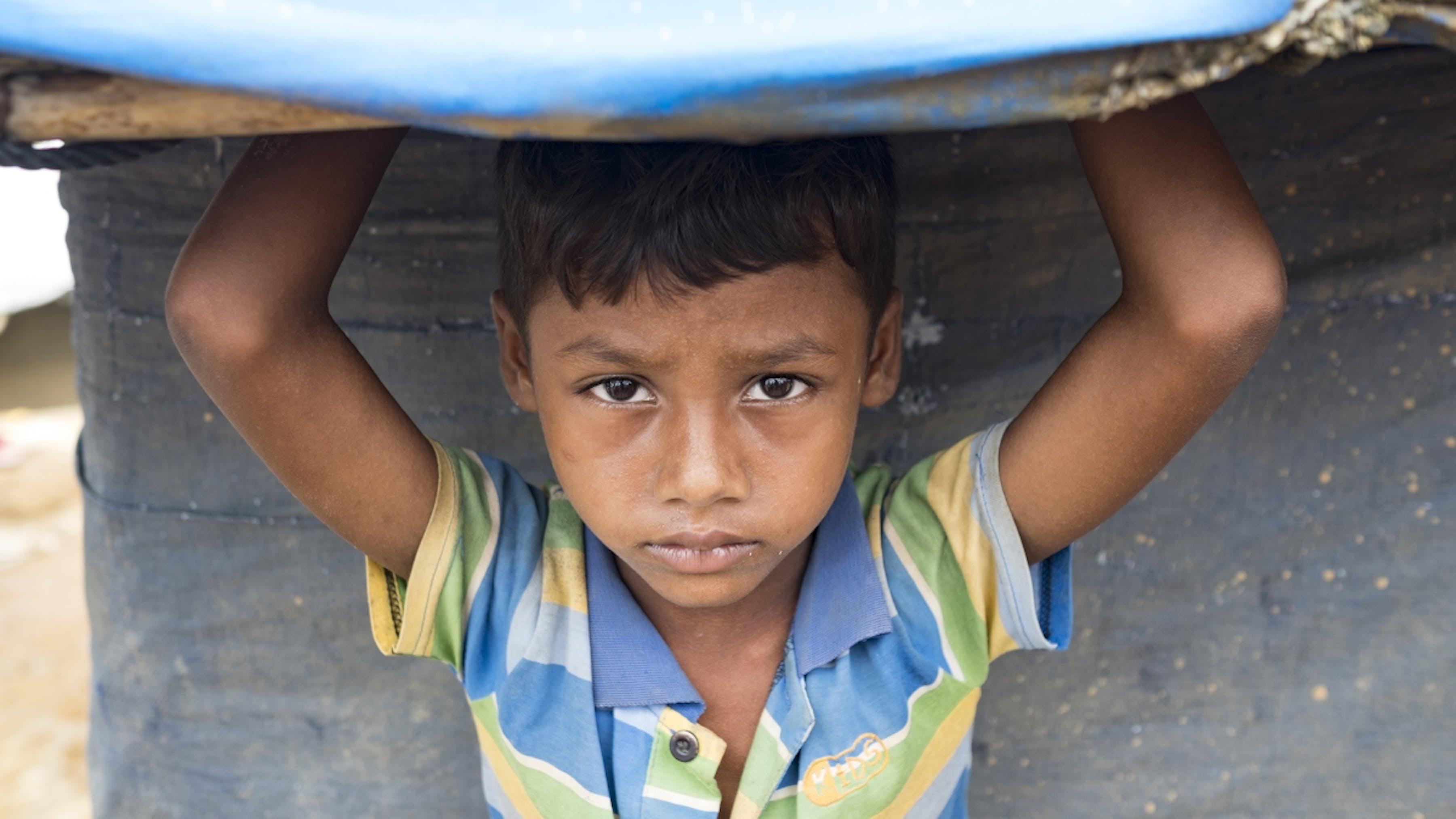 Bangladesh, un bambino cerca sollievo dal sole sotto il tetto di plastica di un rifugio nel campo di Kutupalong