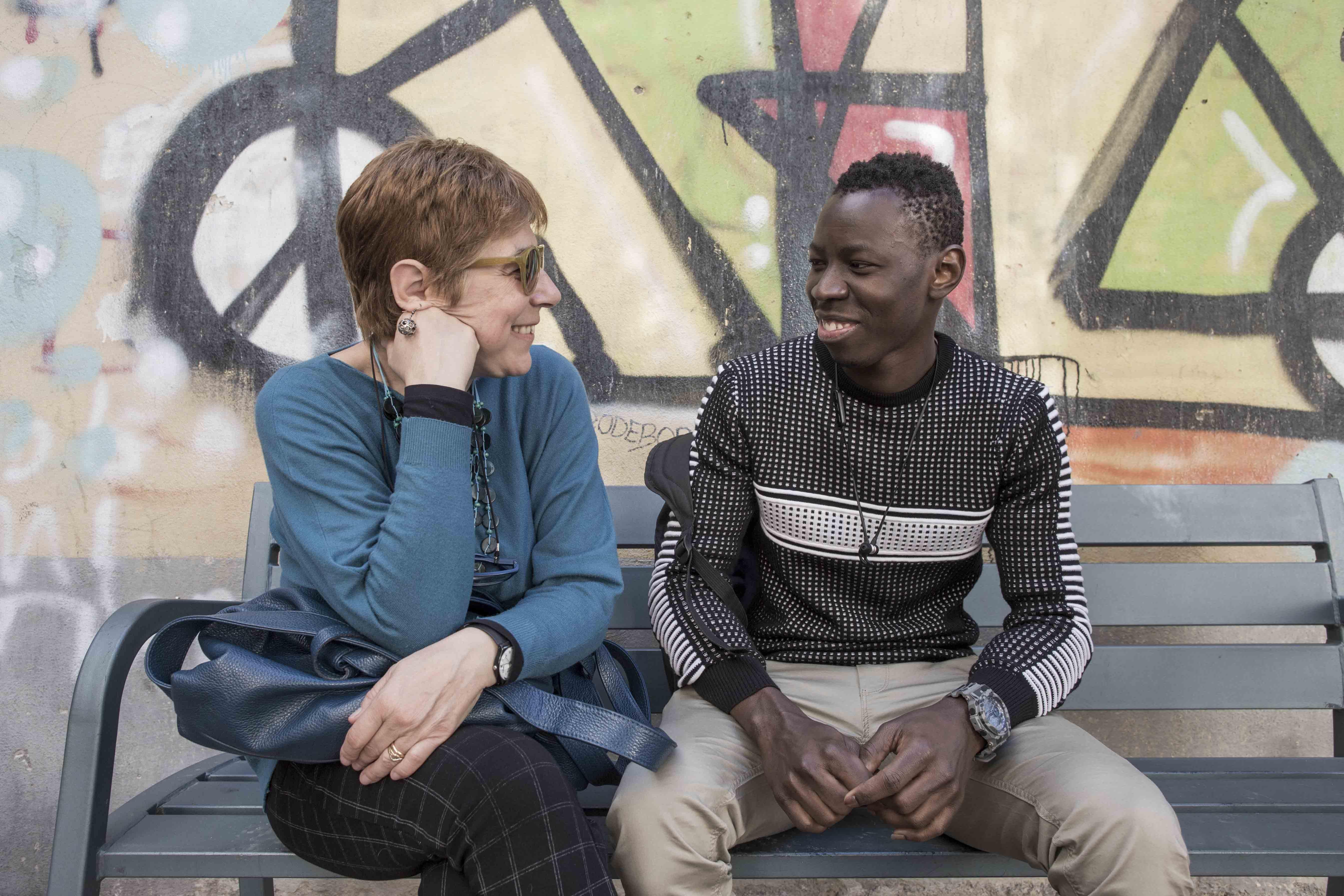 Ragazzo straniero seduto con una donna