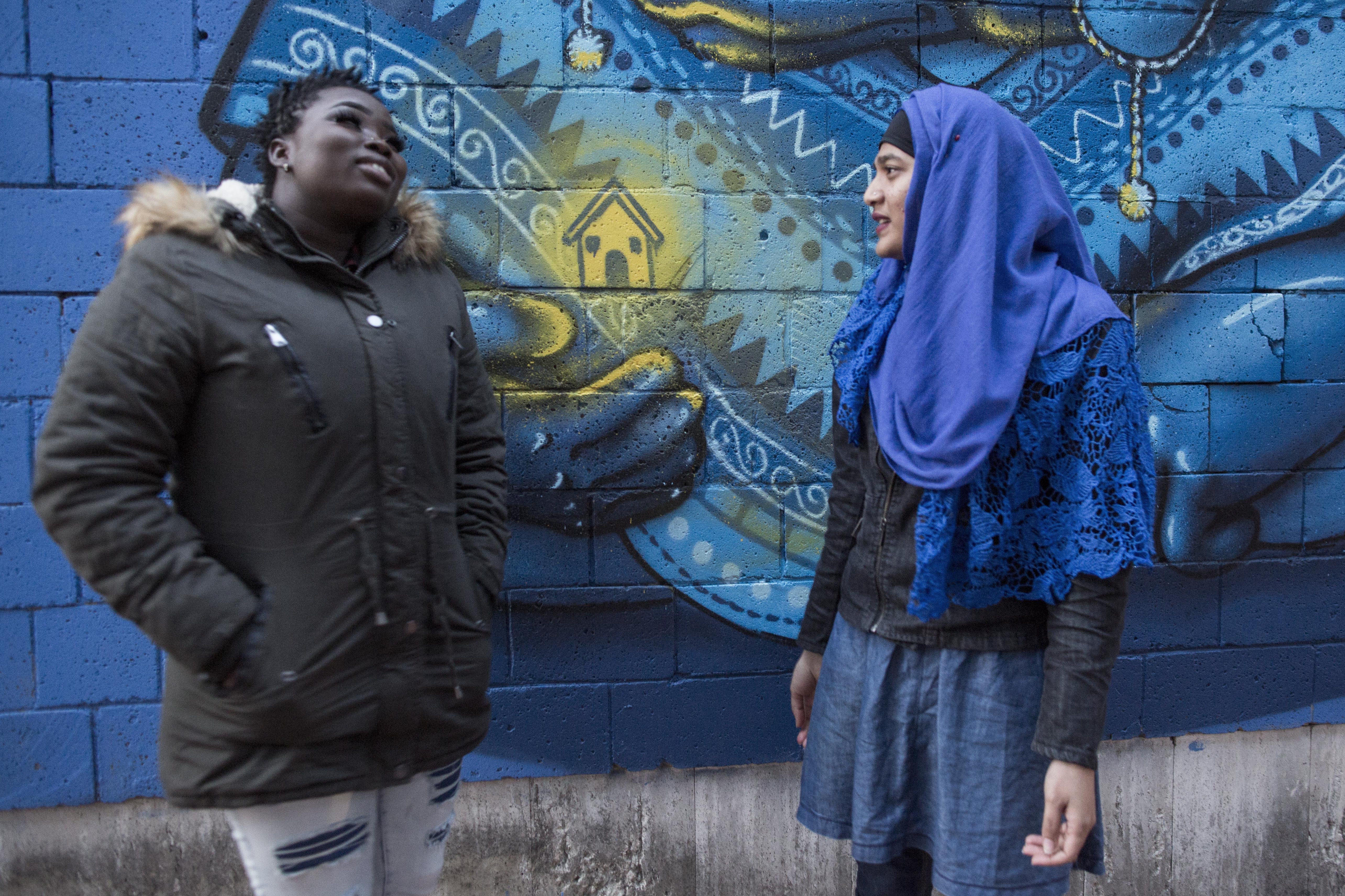 Due giovani donne davanti a un murales