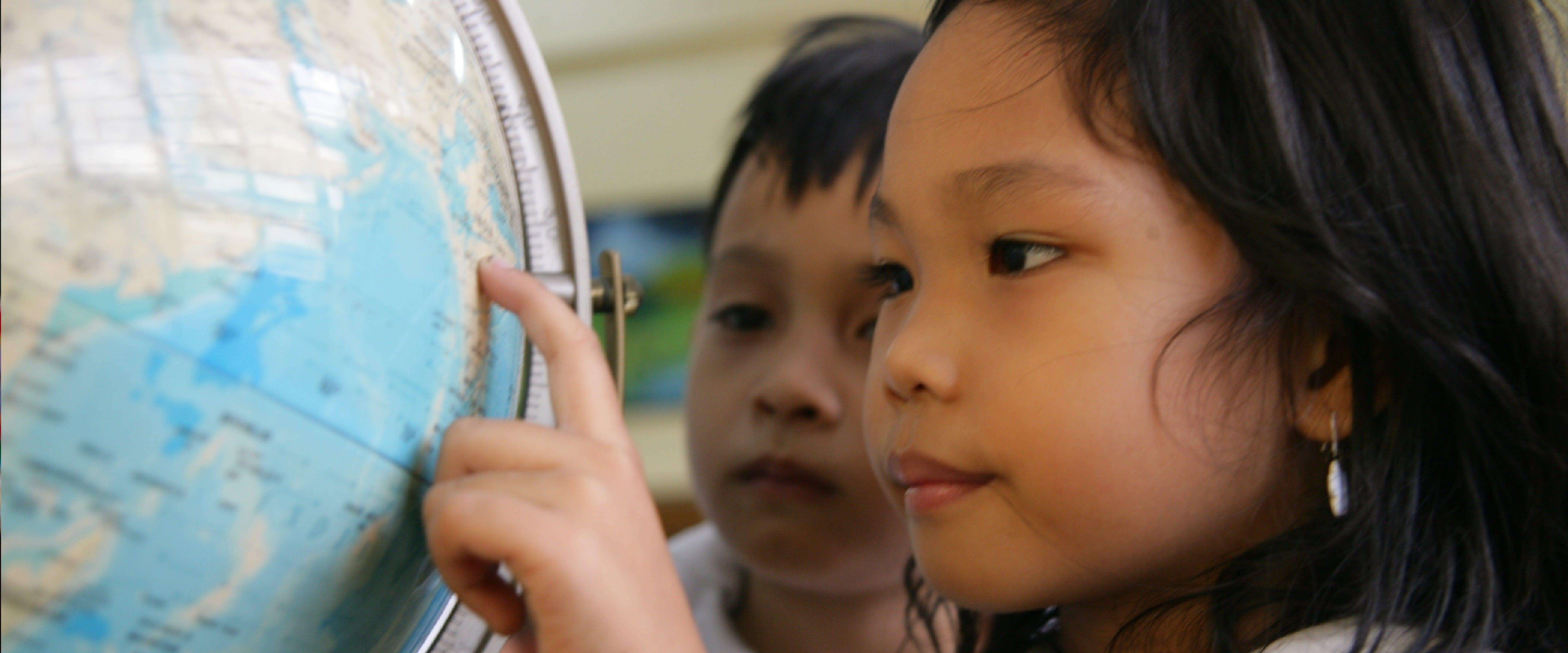 bambina gioca con il mappamondo