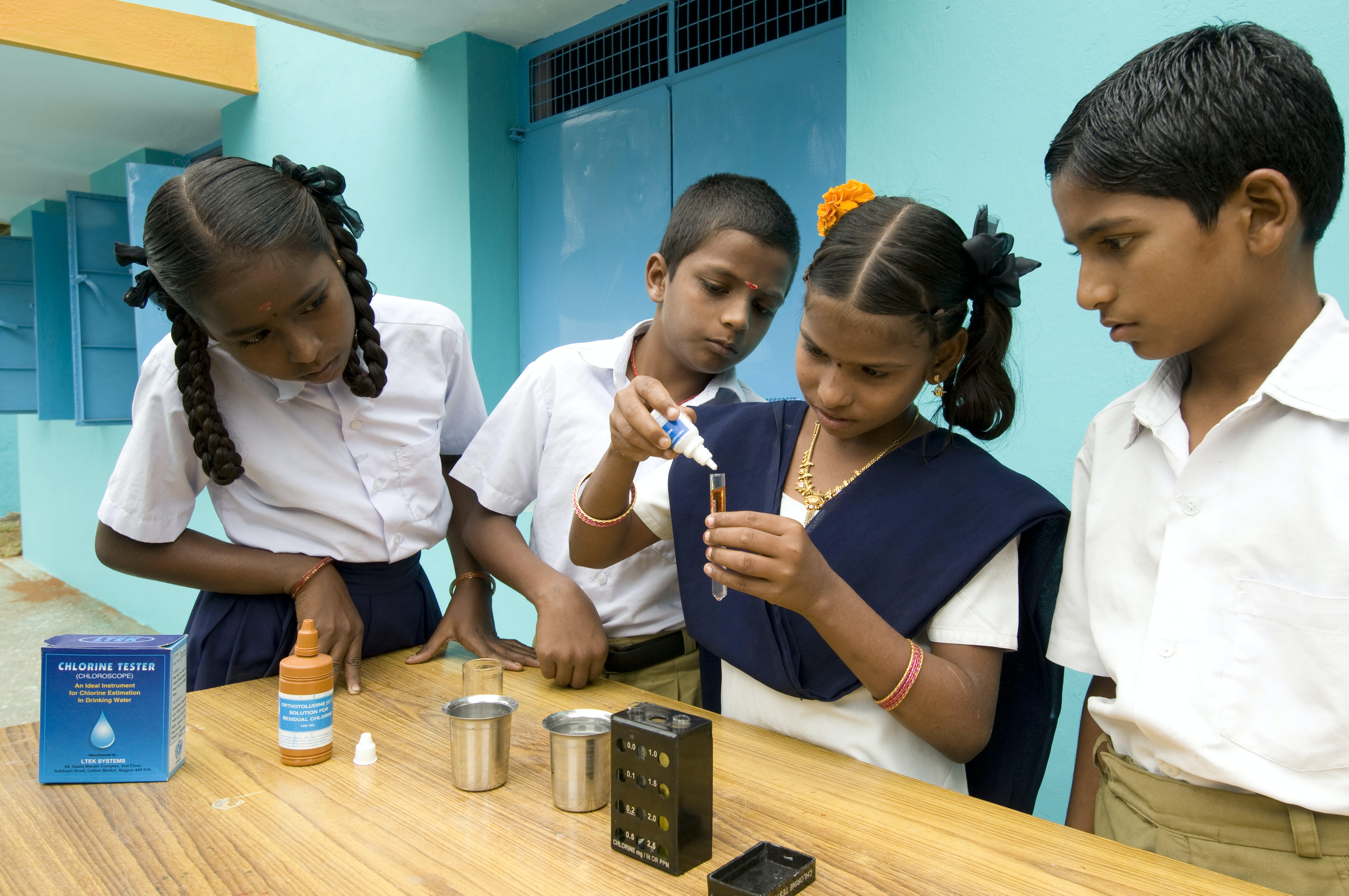 Bambini eseguono un test con il cloro in una scuola in India