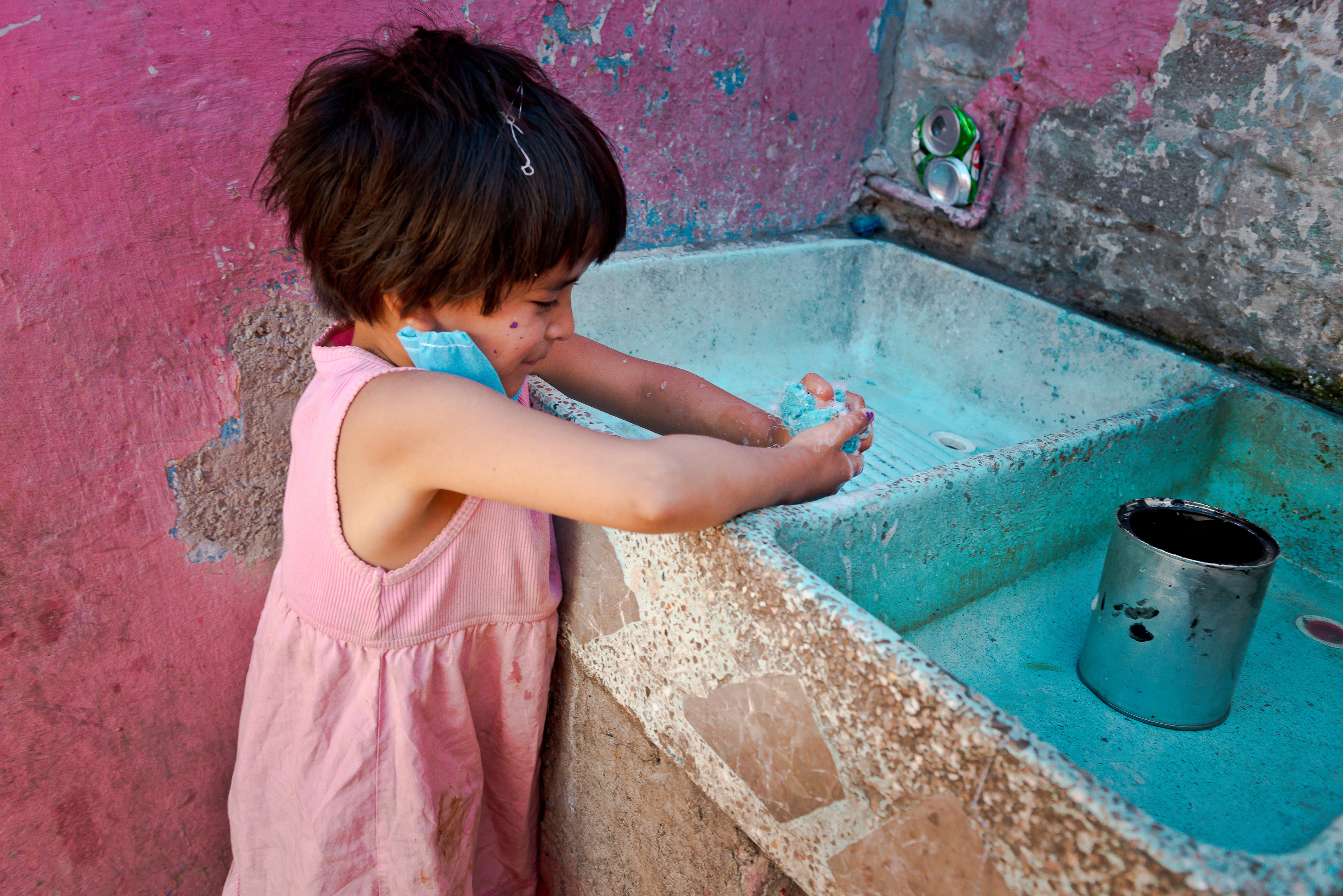 Una bambina si lava con cura le mani per proteggersi dal Covid