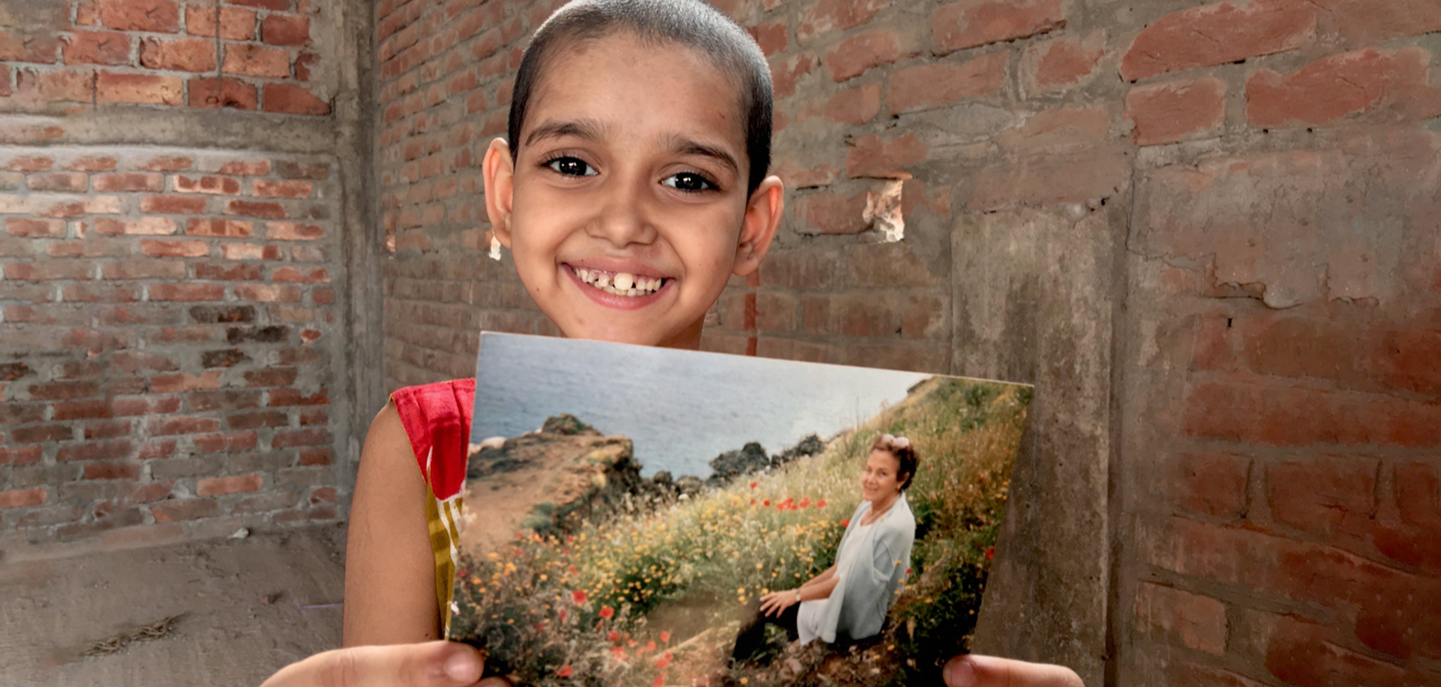 Bambina tiene in mano la foto di una donna
