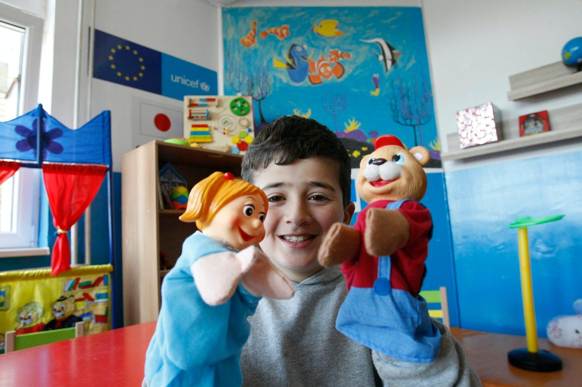 Malik, 10 anni, gioca con le marionette in una Biblioteca