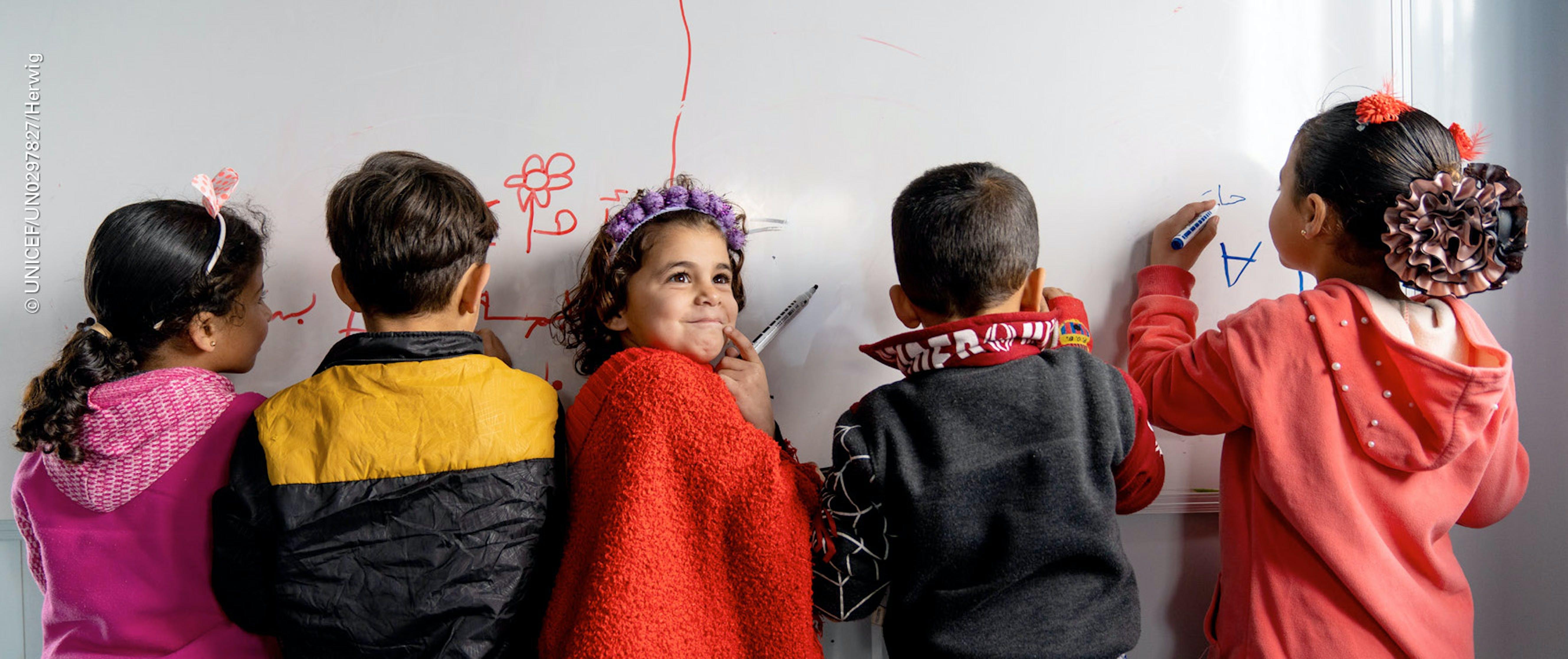 Bambini di spalle colorano su una lavagna