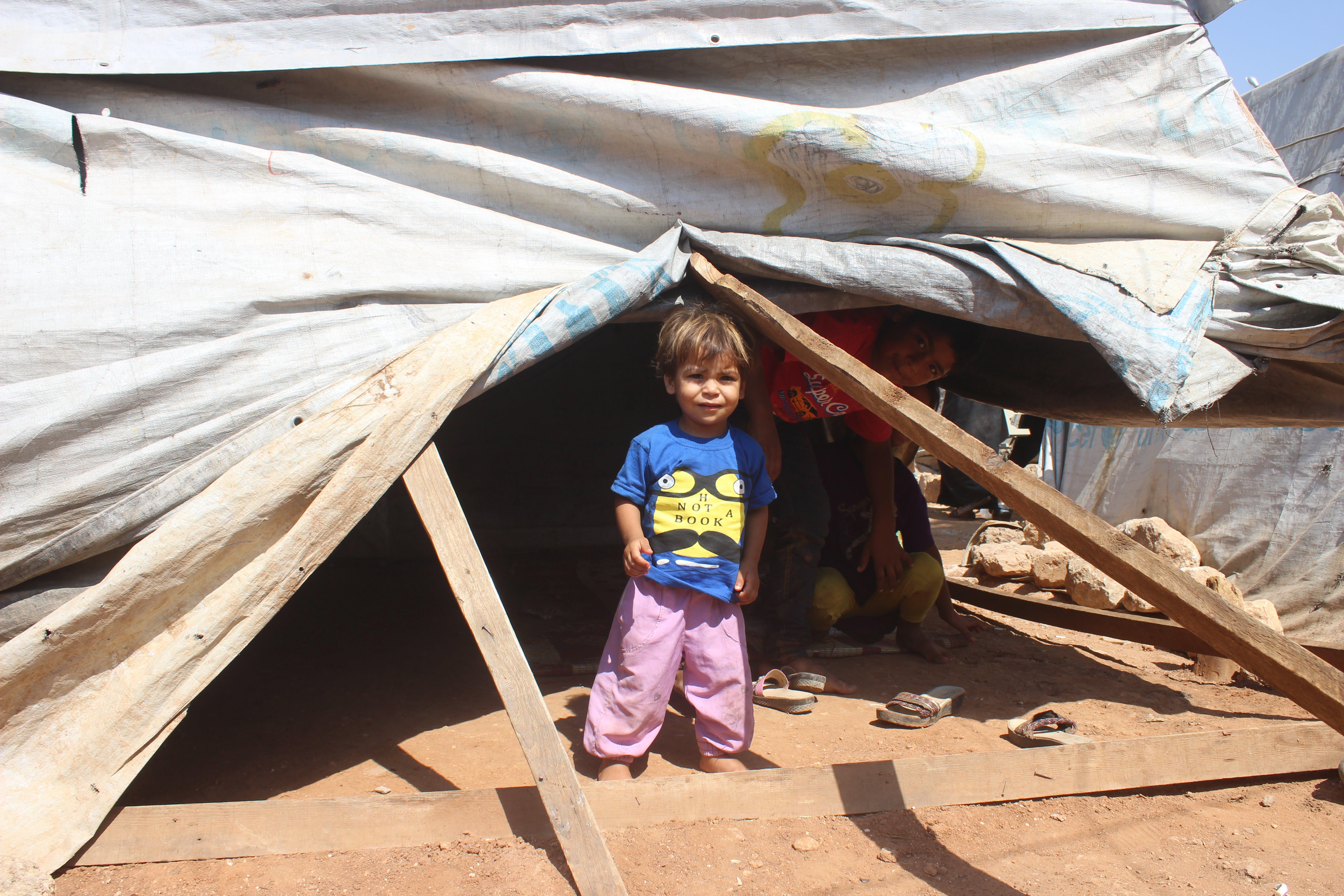 Bambino fuori dalla tenda all'interno del campo profughi Al- Hol in Siria