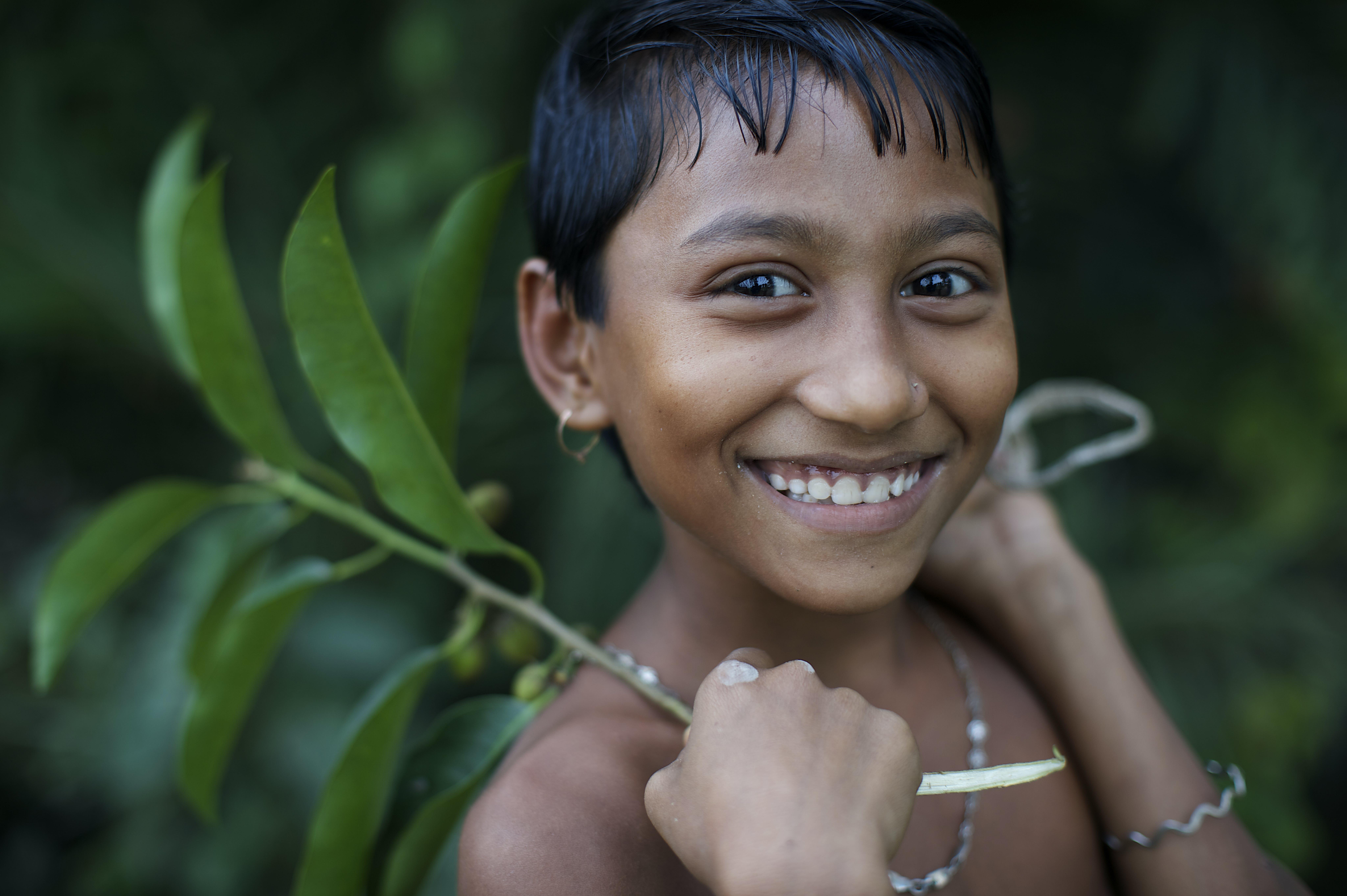 Una bambina con una fronda in mano sorride nel villaggio di Kalaboho, in Bangladesh
