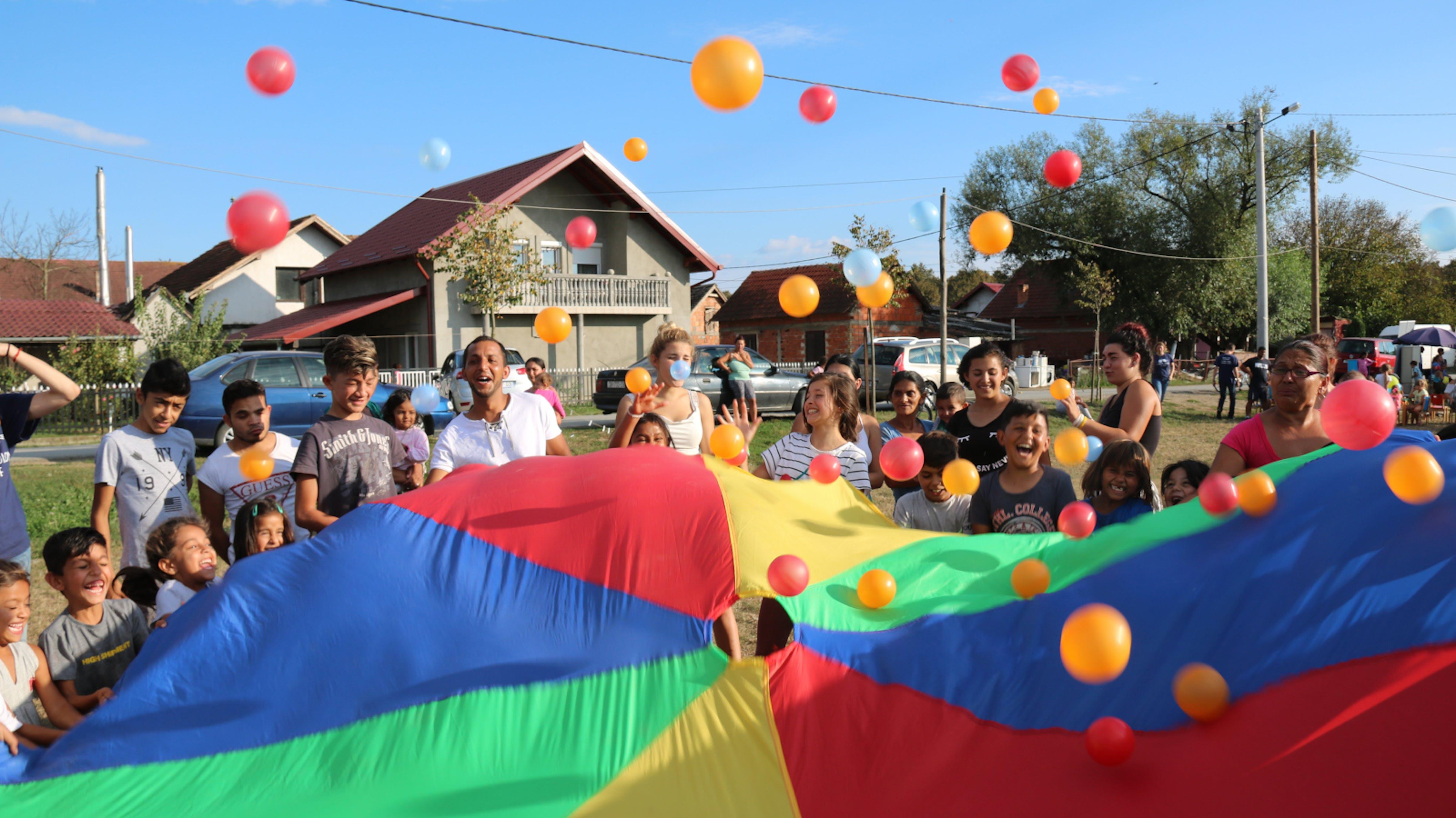 Adulti e bambini giocano con un telo colorato_Utopia