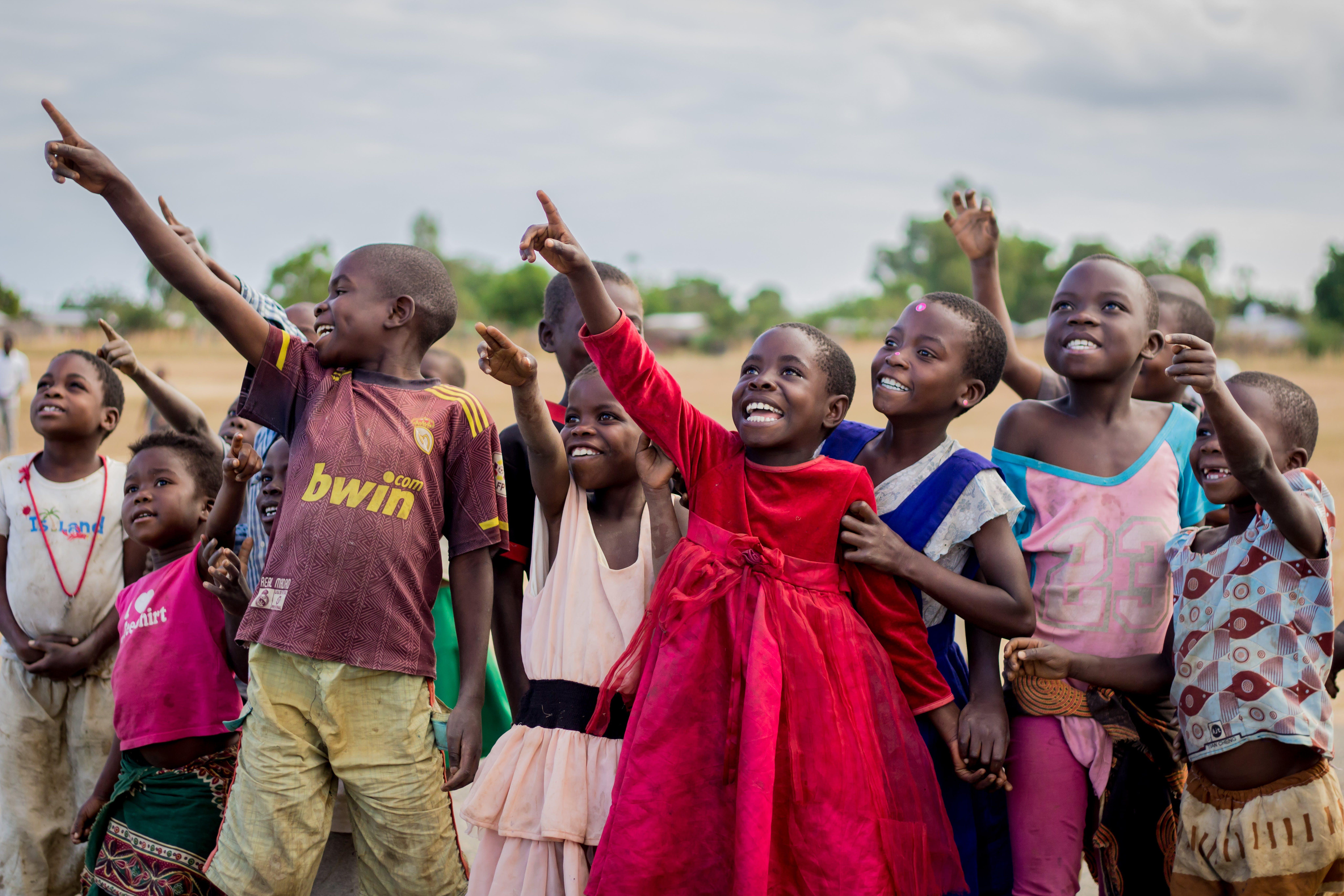 Un gruppo di babini a Vanatu, guardano un drone volare nel cielo, guidato da un operatore UNICEF.