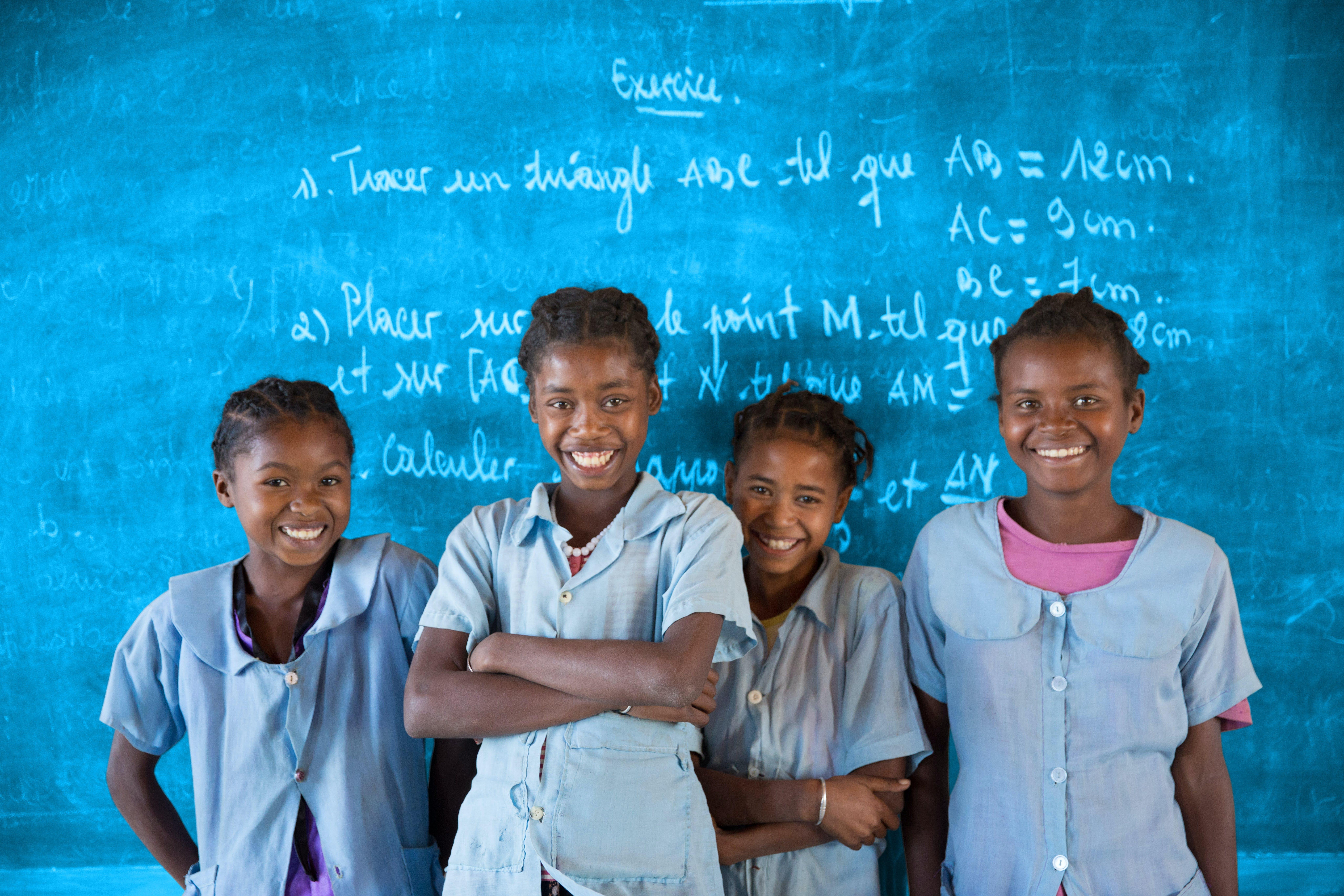 Bambini a scuola sorridono davanti alla lavagna