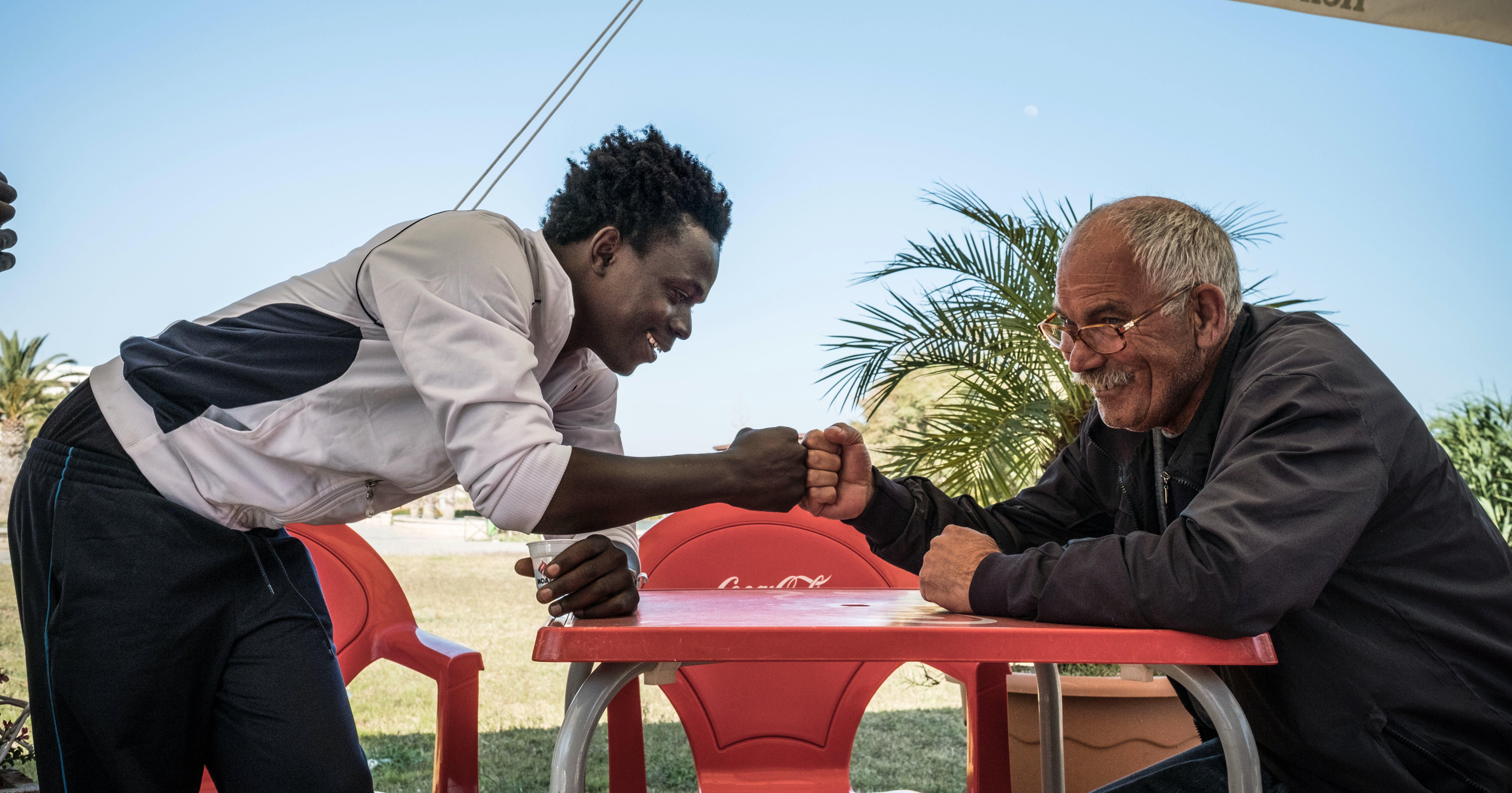 Sicilia, Mohammed si saluta con un anziano signore che ha conosciuto fuori dall'hotspot di Pozzallo