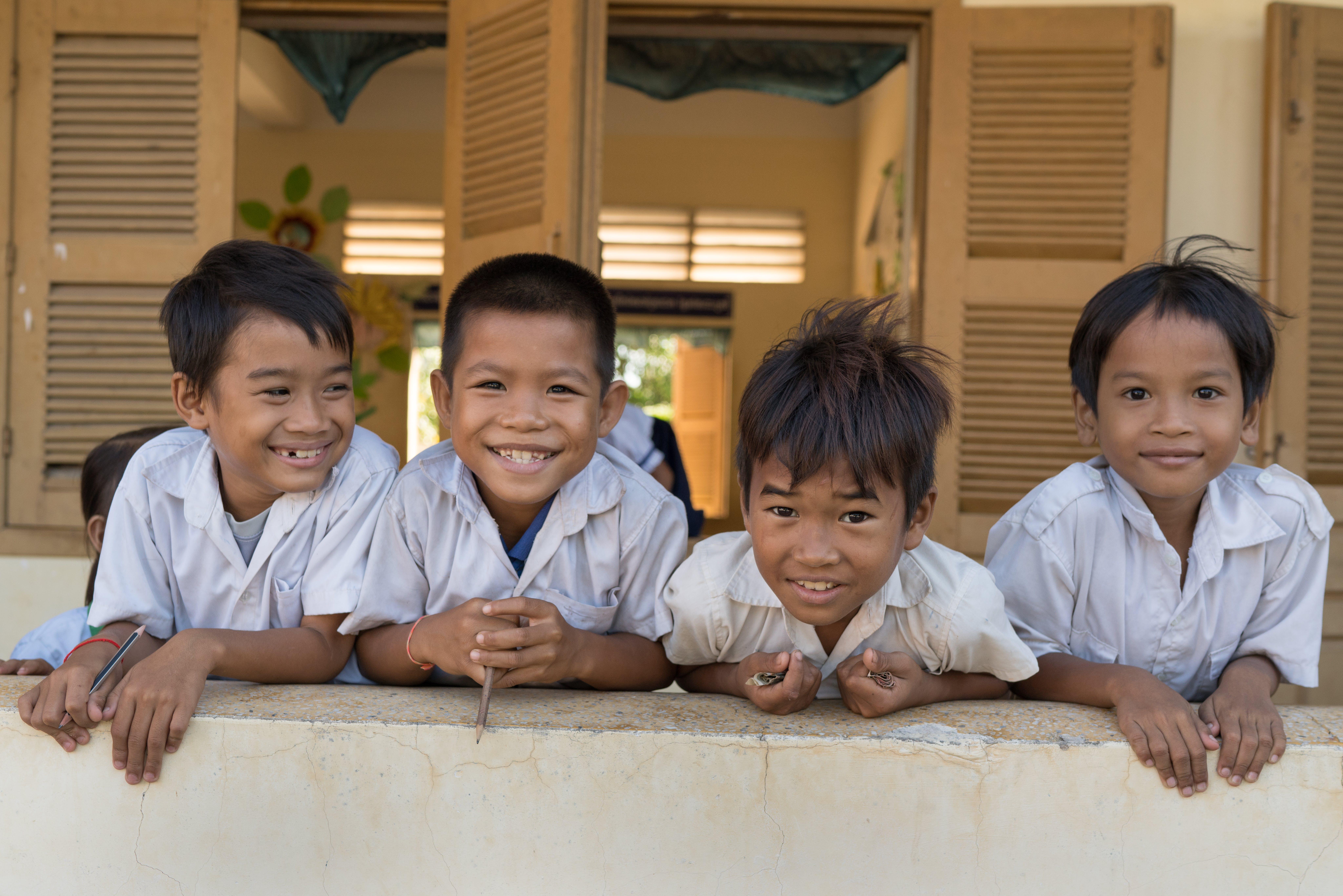 Gruppo di bambini che sorridono fuori dalla scuola elementare di Watanak Chhoung Leap, nel distretto di Sa'ang in Cambogia.