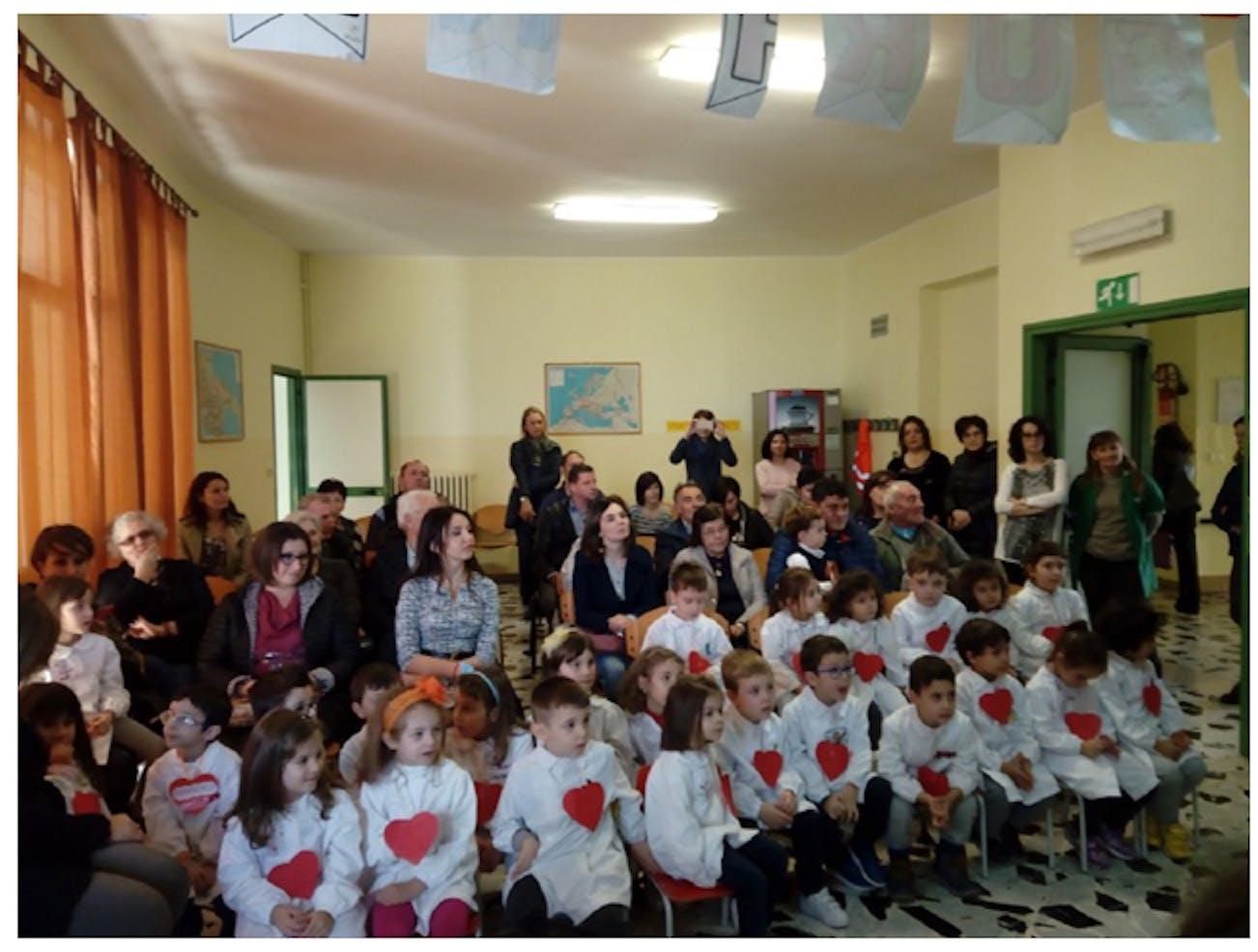I bambini di cinque anni della scuola dell'infanzia con nonni e genitori