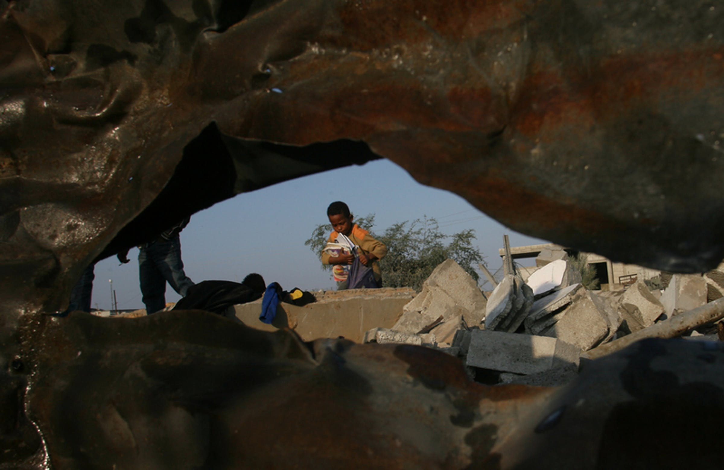 Ahmed (8 anni) recupera libri di scuola e vestiti tra le macerie della sua casa, rimasta distrutta dopo un raid aereo israeliano, nel villaggio di Khan Younis, nel sud della Striscia di Gaza - ©UNICEF/NYHQ2012-1580/El Baba