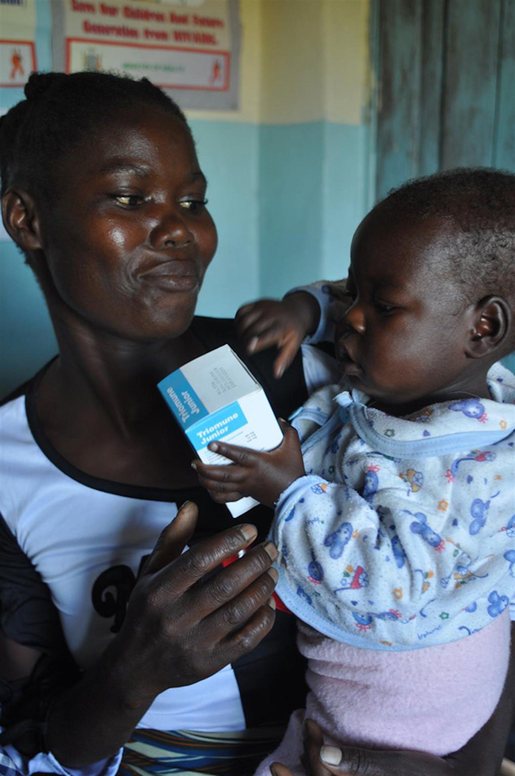 Bright, 21 mesi, stringe tra le mani una confezione di farmaci antiretrovirali, la stessa medicina che la sta proteggendo dal virus HIV che ha ereditato dalla mamma. Qui è con sua zia Leontine, nell'ospedale Chimebe (Zambia) - ©UNICEF/NYHQ2010-0871/Nesbitt
