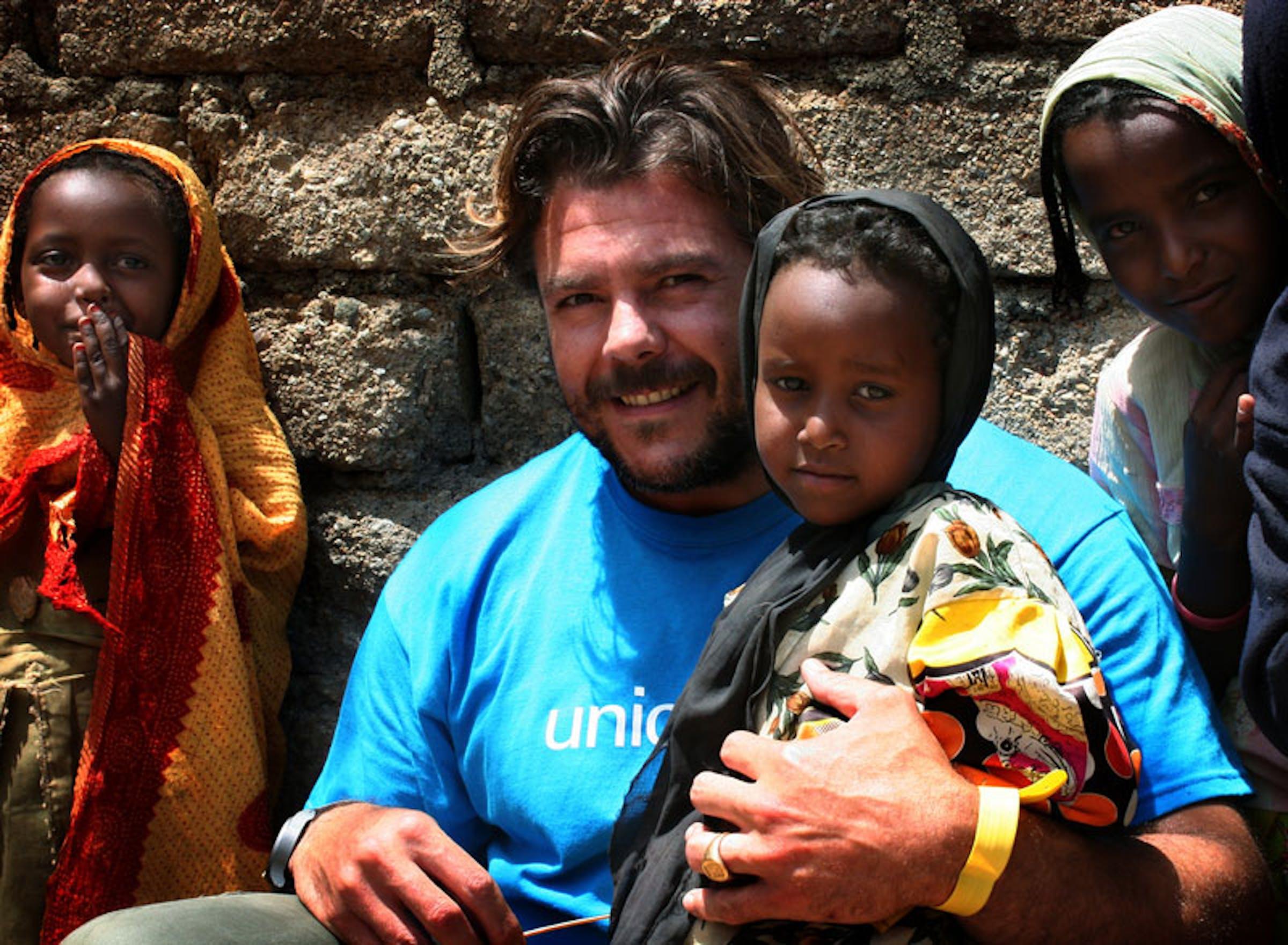 Andrea Lo Cicero, leggendario pilone della Nazionale azzurra di rugby, con un bambino durante la sua recente missione con l'UNICEF in Eritrea - ©UNICEF Italia/2013/Chiara Curto