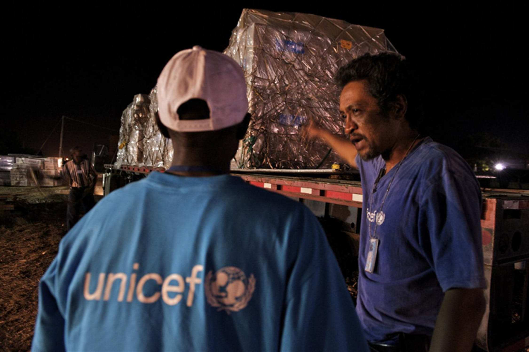 In piena notte, operatori UNICEF nell'aeroporto di Port-au-Prince scaricano beni da un volo umanitario proveniente dagli Stati Uniti