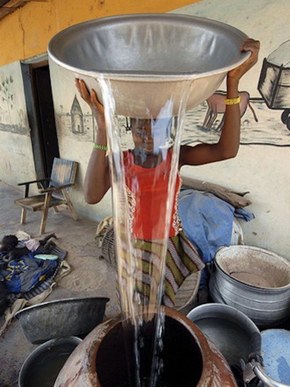 Una bambina versa acqua da una cisterna installata dall'UNICEF nel suo villaggio