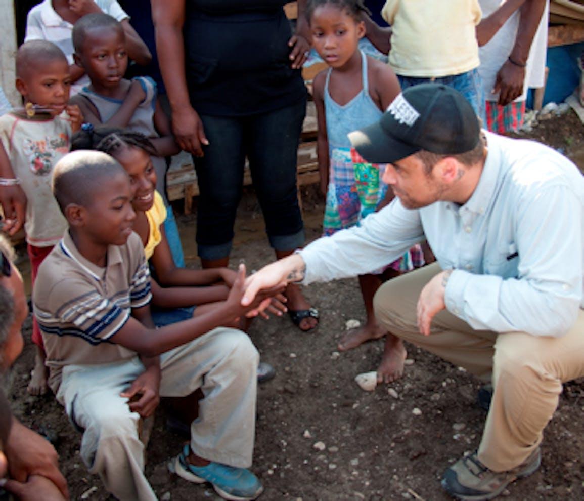 Robbie Williams parla con Denise, 9 anni, e suo fratello, che vivono in una tendopoli a Jacmel (Haiti). Denise è tornata a scuola grazie all'UNICEF - ©Simon Niblett/UNICEF/2010