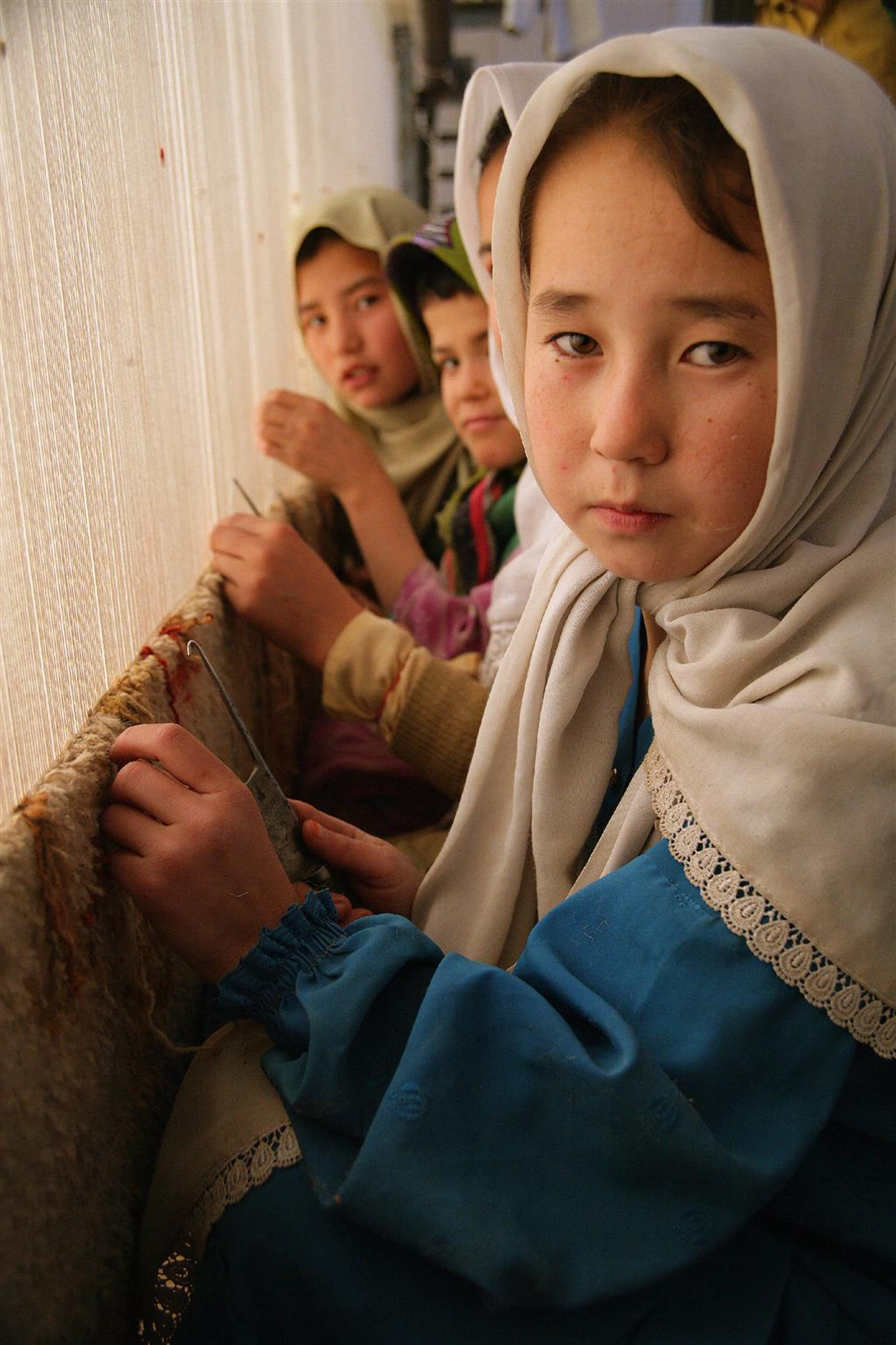 Bambine tessono un tappeto in una grande fabbrica tessile nei dintorni di Quetta, in Pakistan, nonostante nel paese sia illegale lo sfruttamento di manodopera minorile - ©UNICEF/HQ06-0350/G.Pirozzi