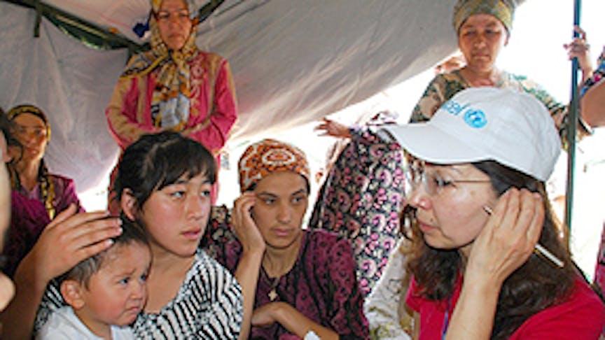 In un campo profughi nel distretto di Hujobod Uzbekistan, un operatore umanitario UNICEF ascolta come Navruza, 14 anni, sia fuggita dalla violenza scatenata in Kirghizistan - ©UNICEF Uzbekistan/2010/Toshmatov