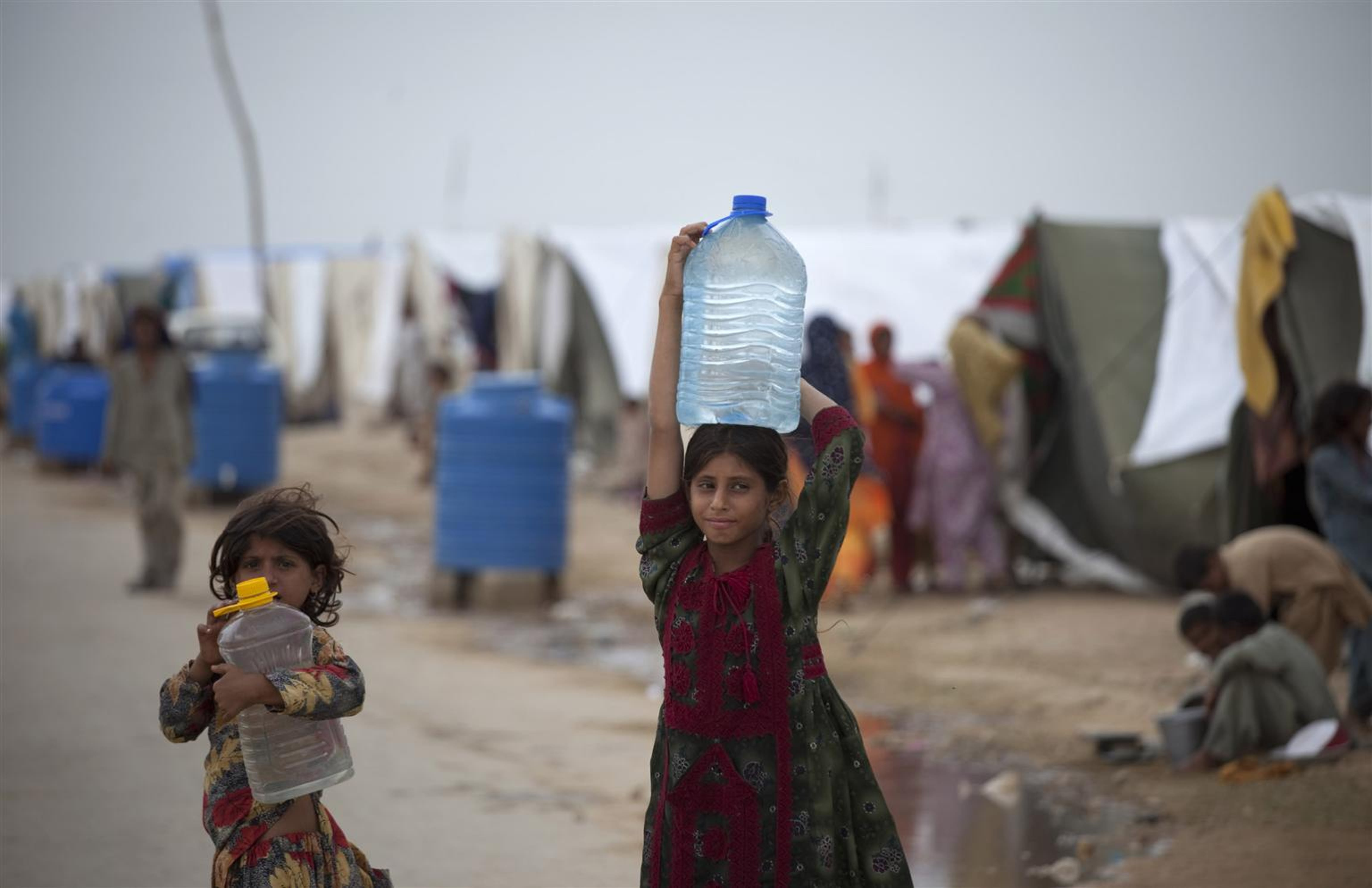 Due bambine trasportano acqua potabile in un campo per sfollati di Karachi (Pakistan): sullo sfondo, alcuni serbatoi idrici installati dall'UNICEF - ©UNICEF Pakistan/2010-275/M.Ramoneda