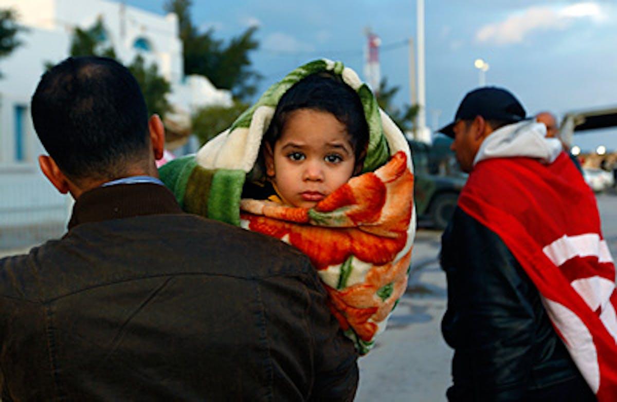 Padre e figlio fuggono dalla Libia al confine di Ras Jdir verso la Tunisia - ©Reuters-Yannis Behrakis