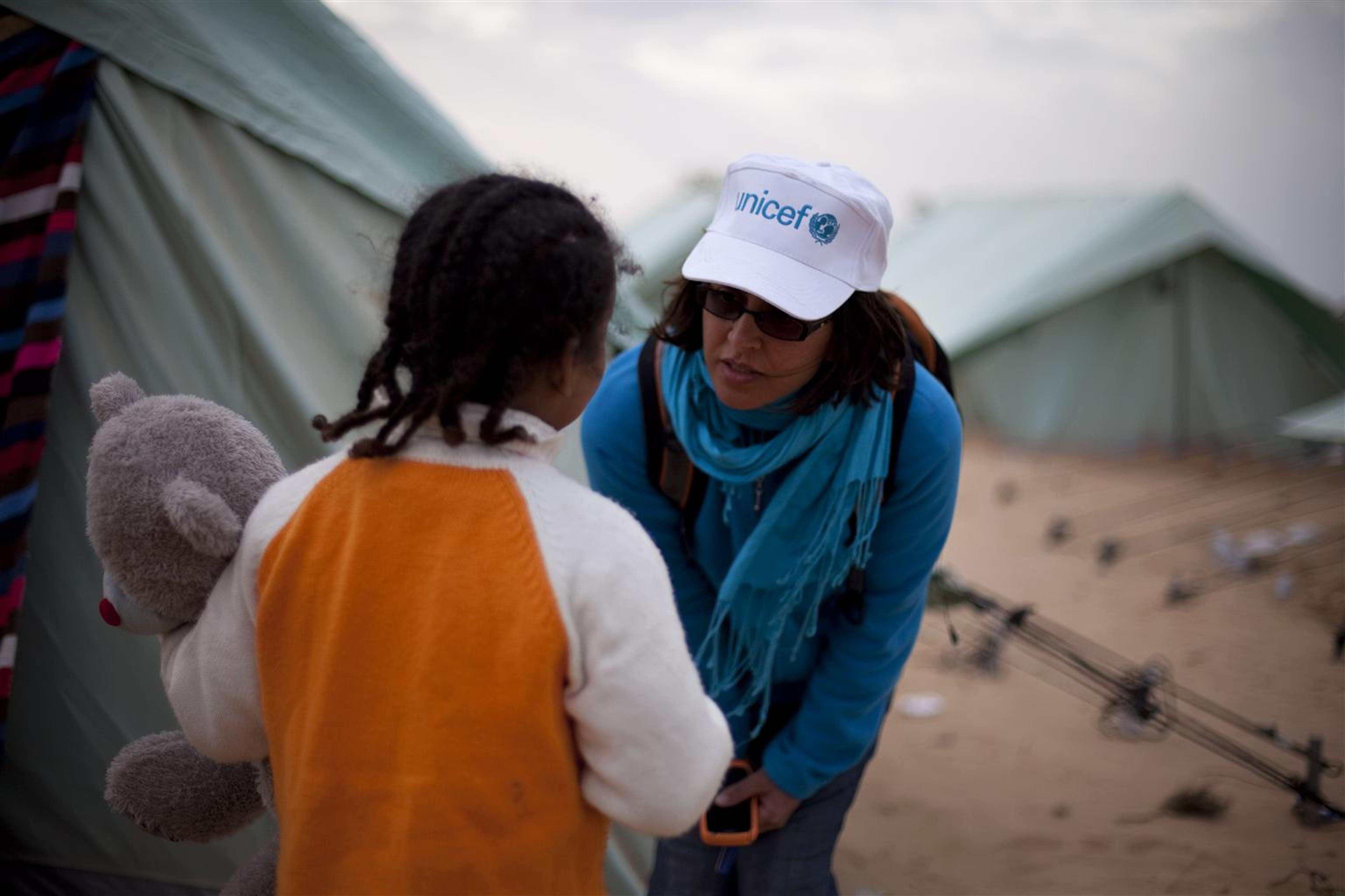 Najwa Mekki, operatrice UNICEF, accanto a Saida (6 anni) in un campo profughi presso il confine tra Libia e Tunisia. Saida, di origine somala, è una rifugiata sin dalla nascita - ©UNICEF/NYHQ2011-0412/Ramoneda
