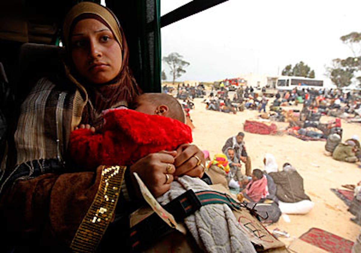 Una donna egiziana con il suo bambino in un campo profughi creato in queste ore al valico di frontiera di Ras Jdir tra Tunisia e Libia - ©Reuters-Zohra Bensemra