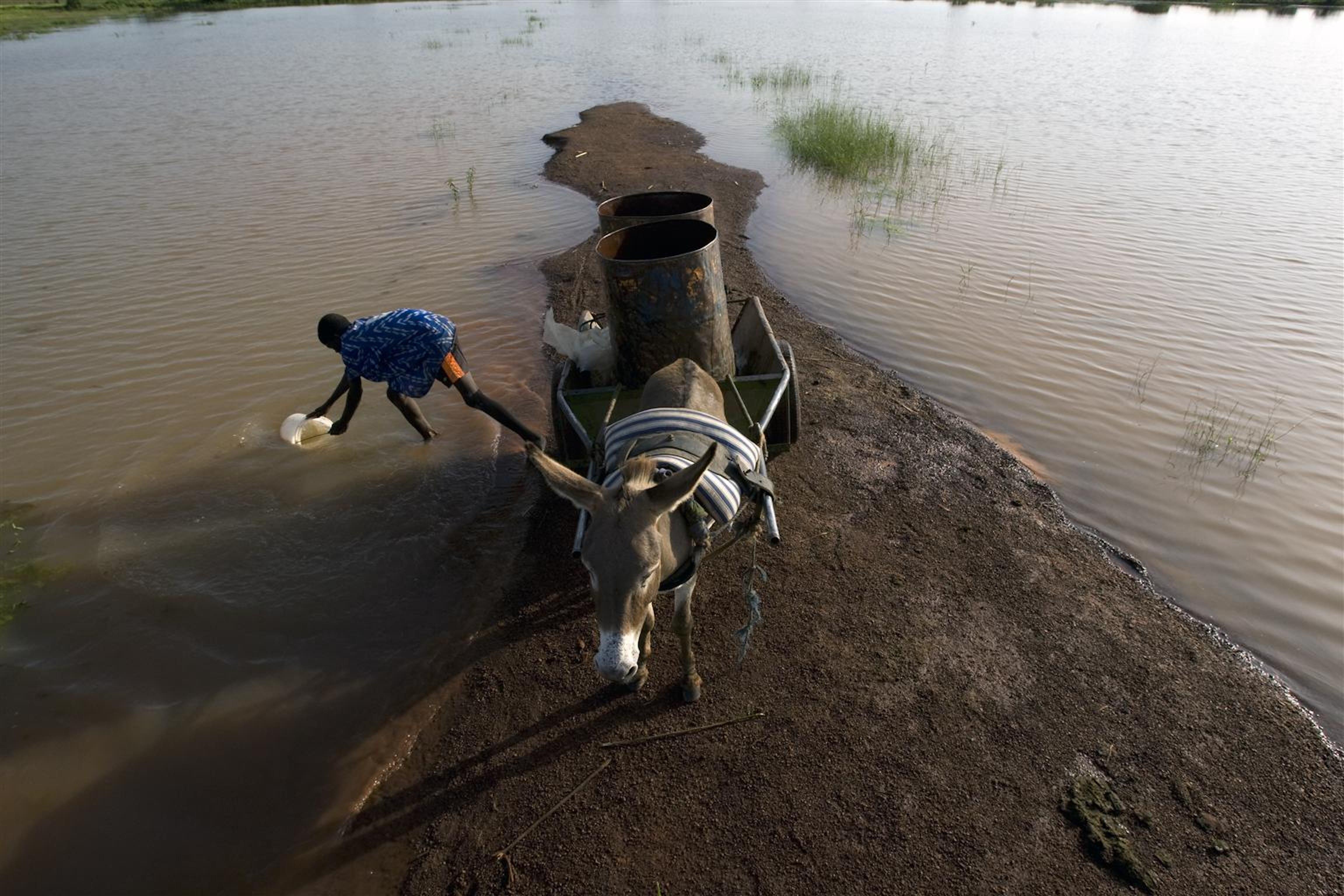 Un ragazzino raccoglie acqua da un fiume presso Savelugu, nel nord del Ghana. L'acqua non è potabile ed è contaminata da parassiti, ma sarà venduta nei villaggi vicini - ©UNICEF/NYHQ2008-0865/O.Asselin