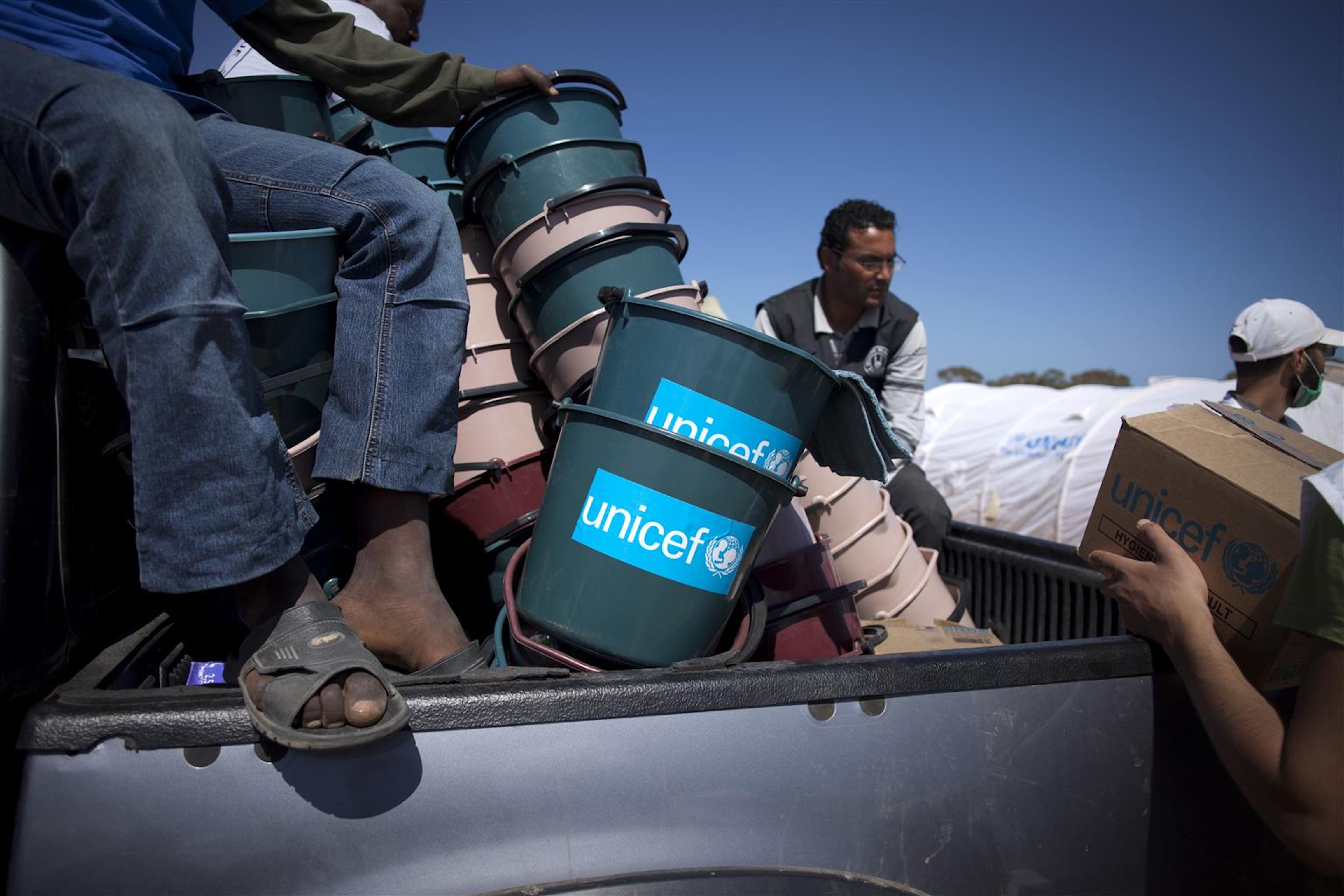 Un camion carico di aiuti UNICEF viene scaricato in un campo profughi al confine tunisino con la Libia - ©UNICEF/NYHQ2011-0508/M.Ramoneda