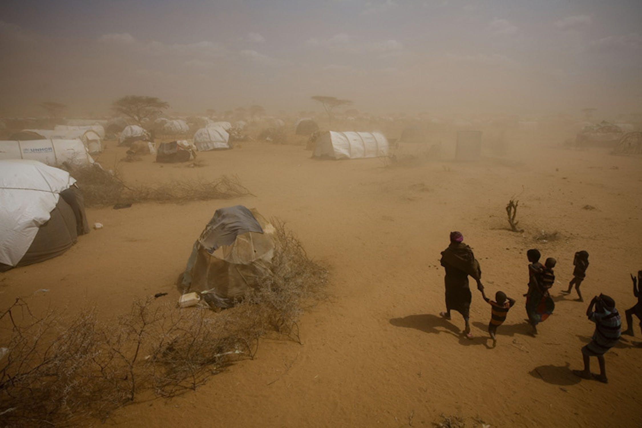 Una donna con i suoi figli avanza in una tempesta di sabbia nel campo profughi di Dagahaley, al confine tra Kenya e Somalia - ©UNICEF/NYHQ2011-1019/K.Holt