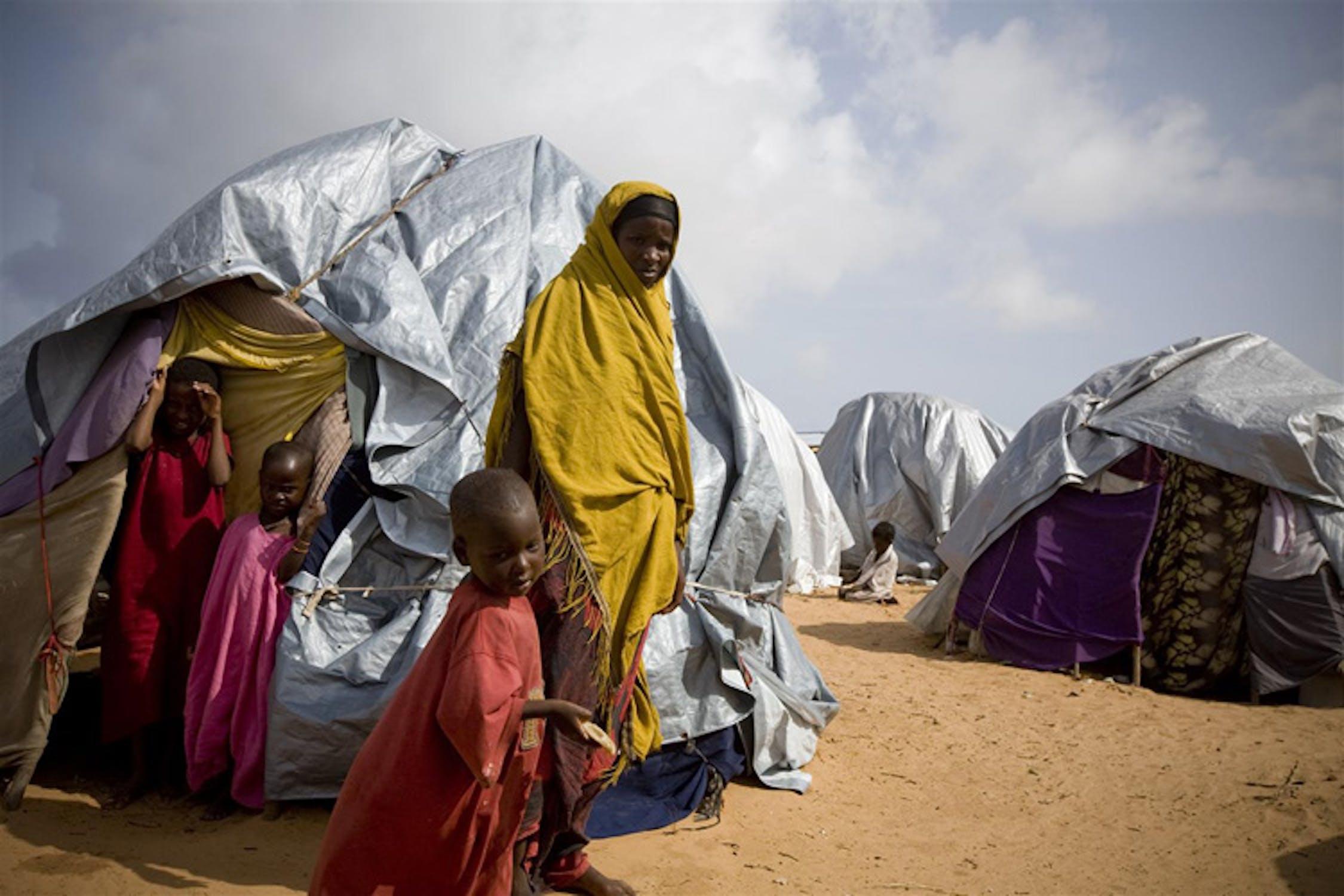 Una donna e i suoi figli accanto alla sua tenda nel campo per sfollati di Badbado, presso Mogadiscio (Somalia). In queste condizioni vivono circa 30.000 persone, in maggioranza donne e bambini - ©UNICEF/NYHQ2011-1185/K.Holt