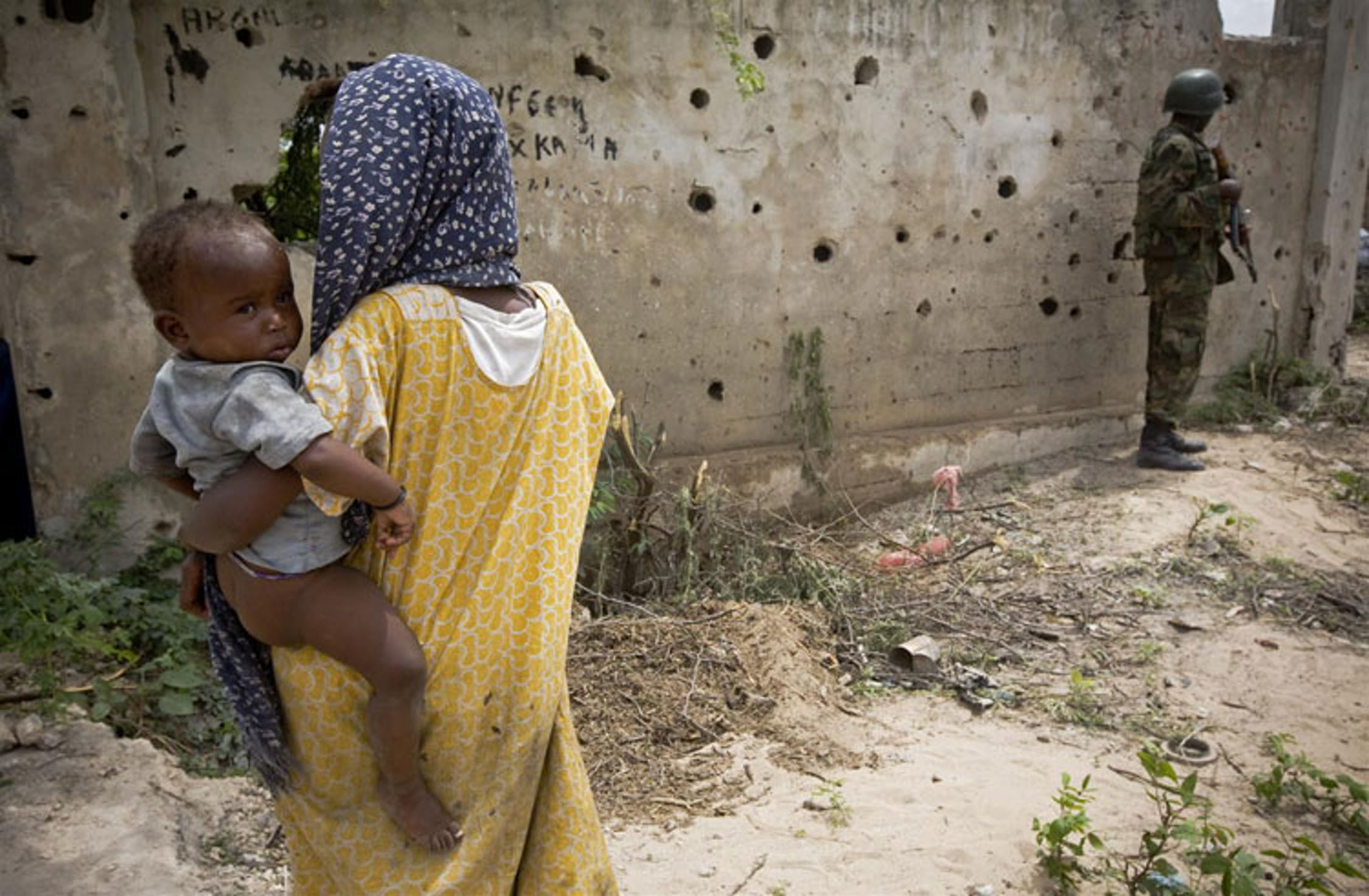 Un muro crivellato dai proiettili, un uomo armato, desolazione intorno: il panorama abituale di un campo per sfollati a Mogadiscio, Somalia - ©UNICEF/NYHQ2011-1194/K.Holt