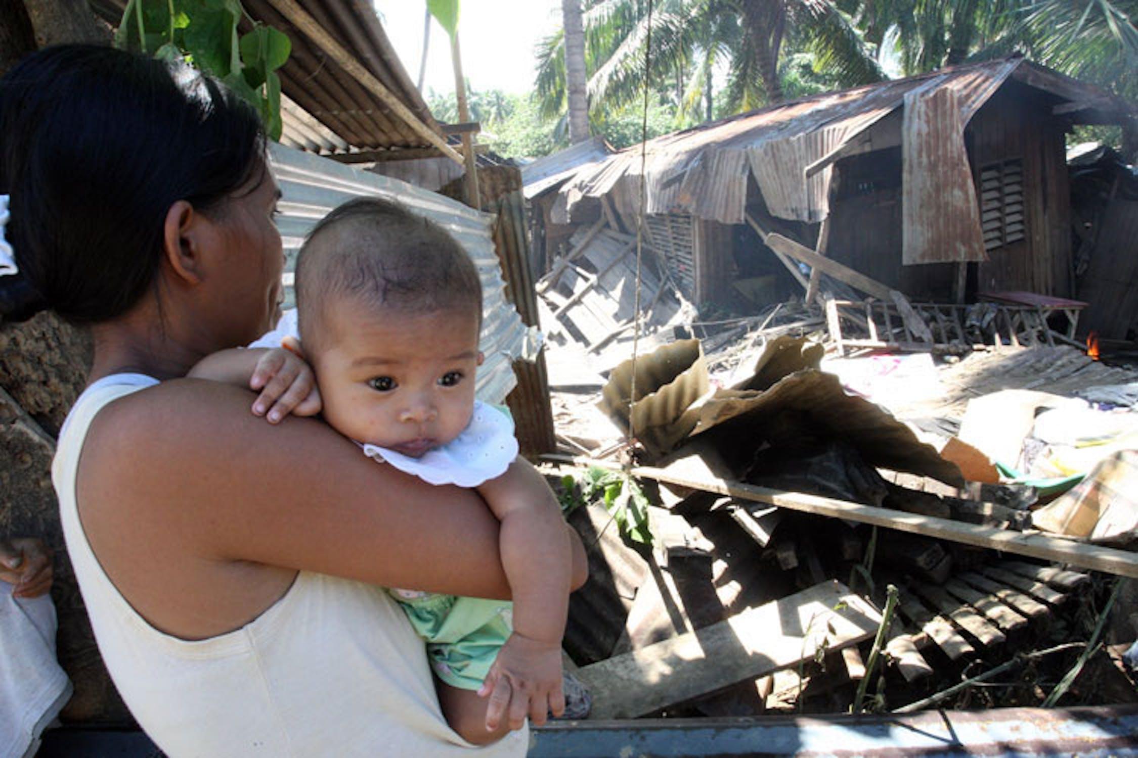 La piccola Marry, 4 mesi, in braccio alla mamma di fronte alle macerie della sua casa - ©UNICEF Filippine/2011/Maitem