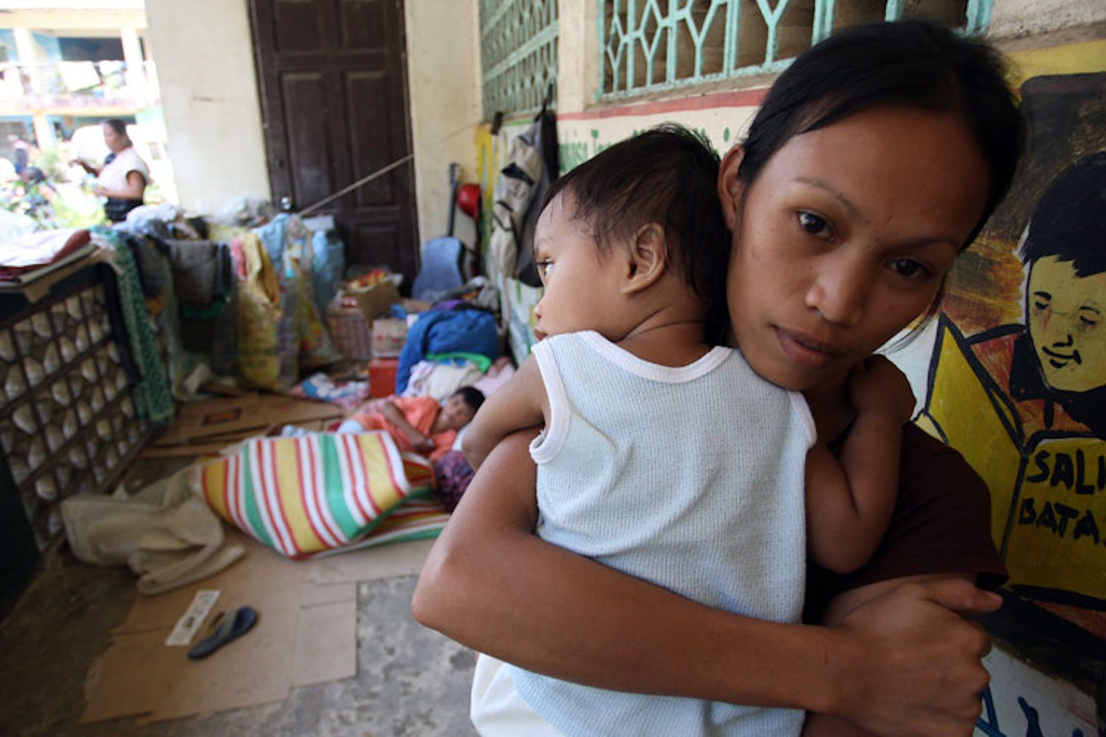 Rossie, 21 anni, stringe suo figlio Clifford (12 mesi) in un centro per sfollati di Cagayan de Oro, la città maggiormente colpita dalla tempesta Washi - ©UNICEF/NYHQ2011-2134/Maitum