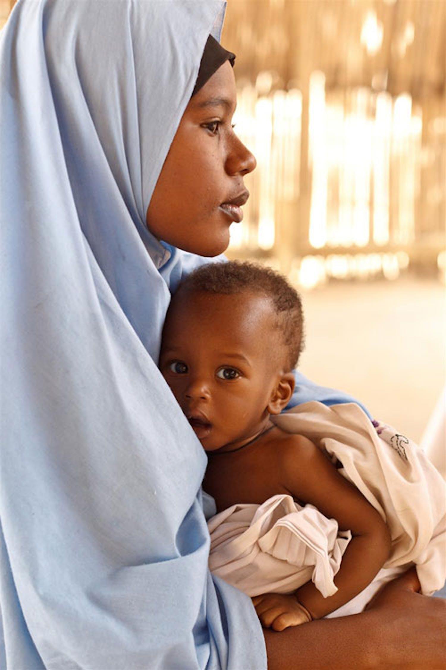 Farida, 16 anni, tiene in braccio il fratellino Laouli, 9 mesi, che attende di essere visitato in un centro nutrizionale terapeutico nella città di Mirriah (Niger) - ©UNICEF/NYHQ2012-0176/Asselin