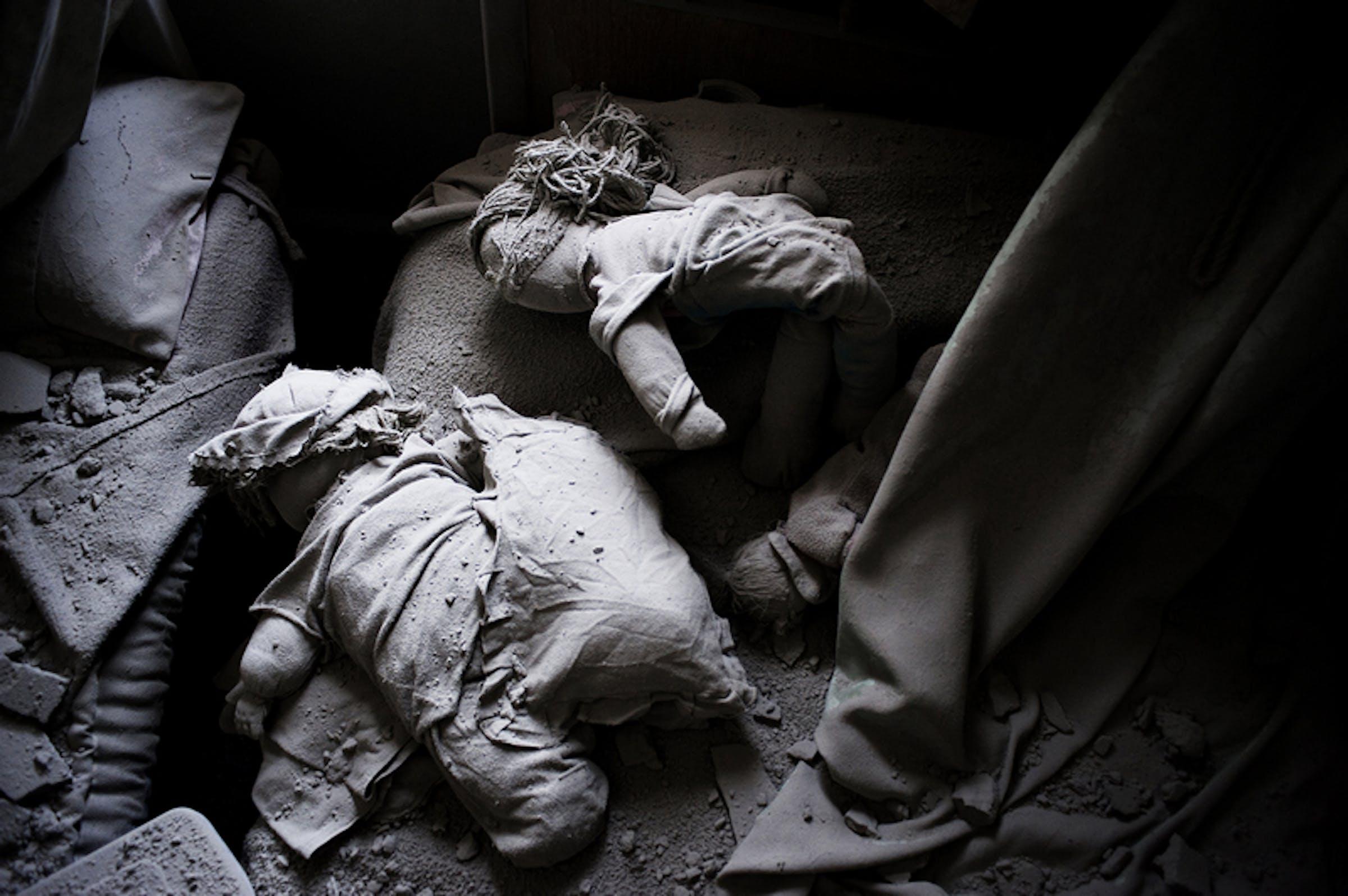 Bambole tra le macerie di una abitazione bombardata in una città della Siria - ©UNICEF/NYHQ2012-0207/A.Romenzi