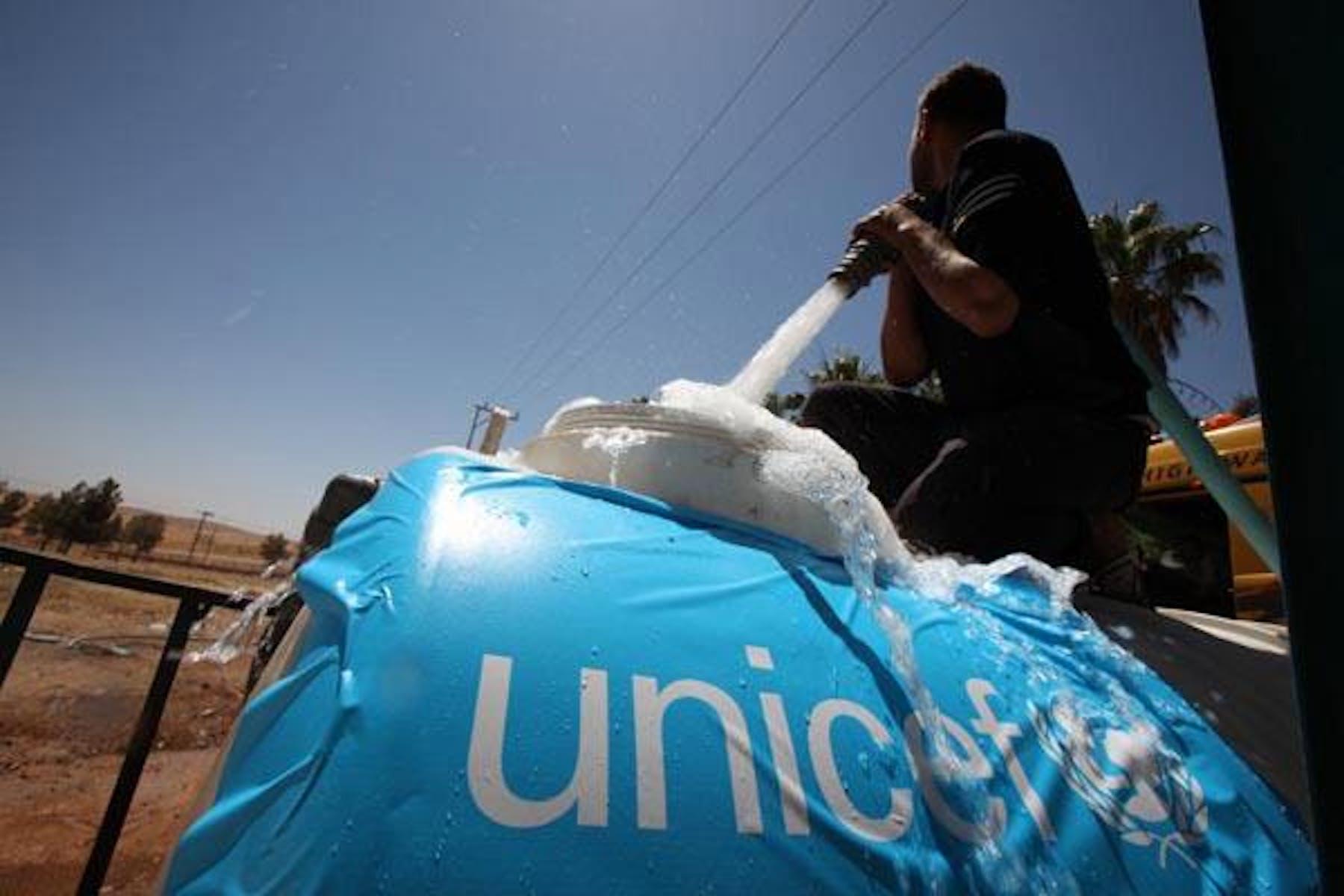 Campo Zaatari (Giordania). Un operatore UNICEF riempie un serbatoio d'acqua utile per soddisfare le esigenze igienico-sanitarie dei rifugiati. ©UNICEF